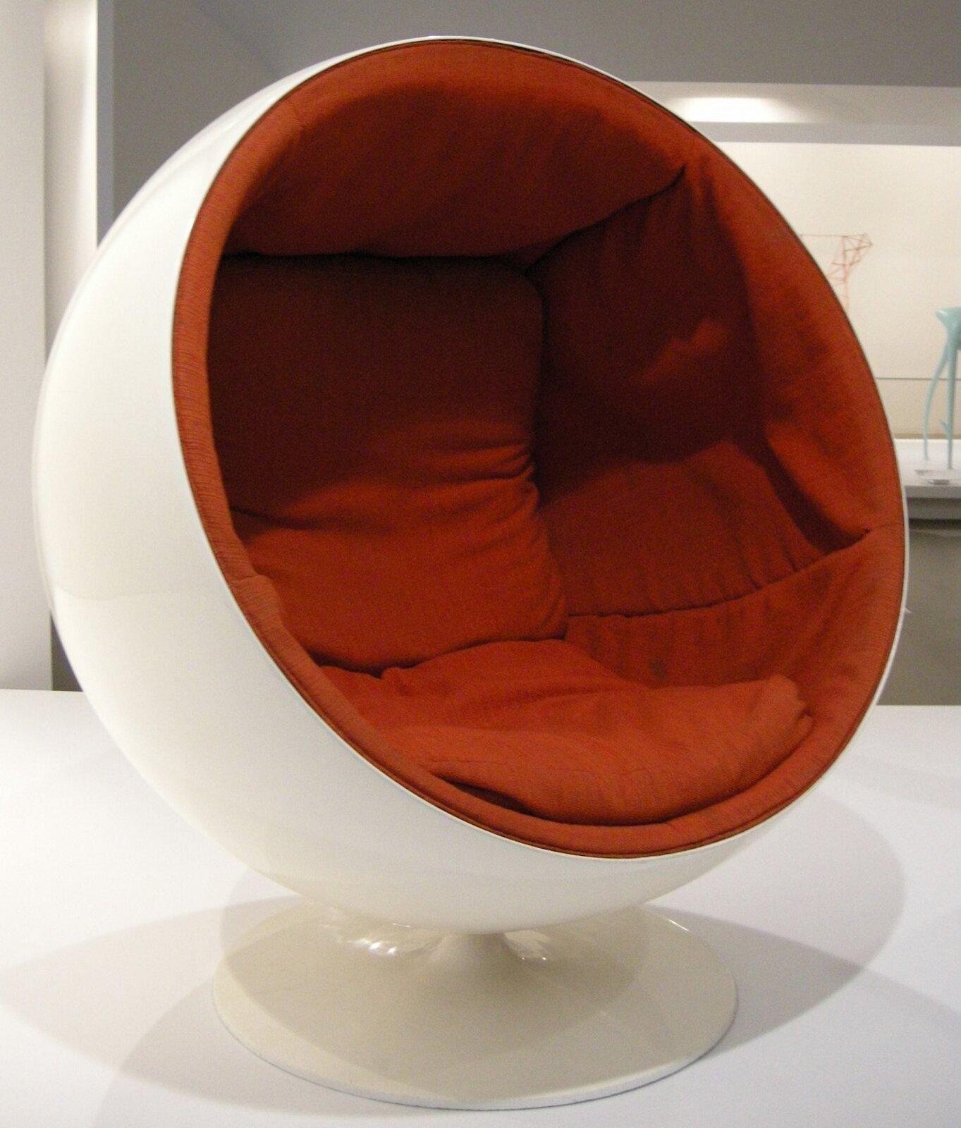 Ilustracja interaktywna przedstawia krzesło zaprojektowane przez Eero Aarnio. Krzesło stanowi wgłównej części wielką półkulę, wktórej jest umieszczone siedzisko. Półkula jest biała, siedzisko natomiast pomarańczowe. Cała konstrukcja utrzymana jest na niewielkiej białej stopce. Mebel pomimo wielkich rozmiarów stanowi estetyczną kompozycję.