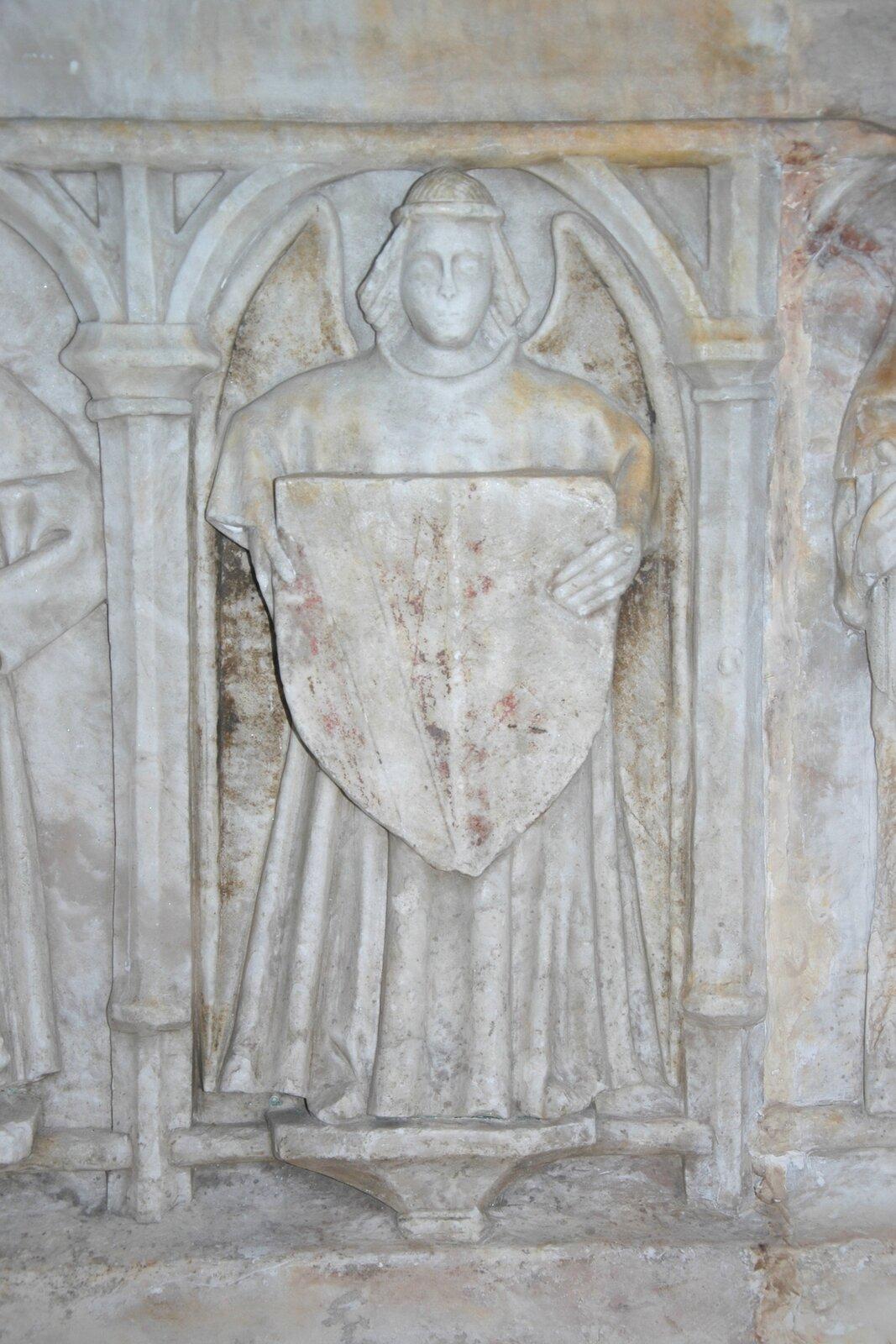 Ilustracja przedstawia detal rzeźbiarski zkościoła St. Mary the Virgin. Na zdjęciu znajduje się płasko wyrzeźbiony wizerunek mężczyzny wdługiej szacie zwłosami do ramion, przepasanymi na czole. Trzymająca wrękach herb postać wpisana jest wmotyw architektoniczny, stoi pomiędzy kolumnami połączonymi nad jej głową łukiem. Cały motyw płasko przylega do ściany.