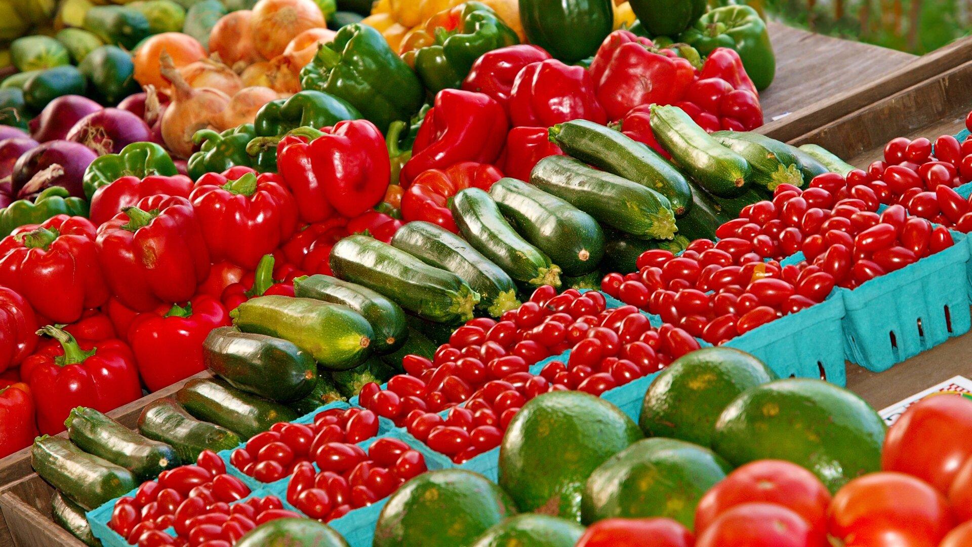 Zdjęcie przedstawia poukładane wrzędach różne warzywa. Między innymi jest widoczny rząd czerwonych papryk, rządek cukinii irząd pomidorów.