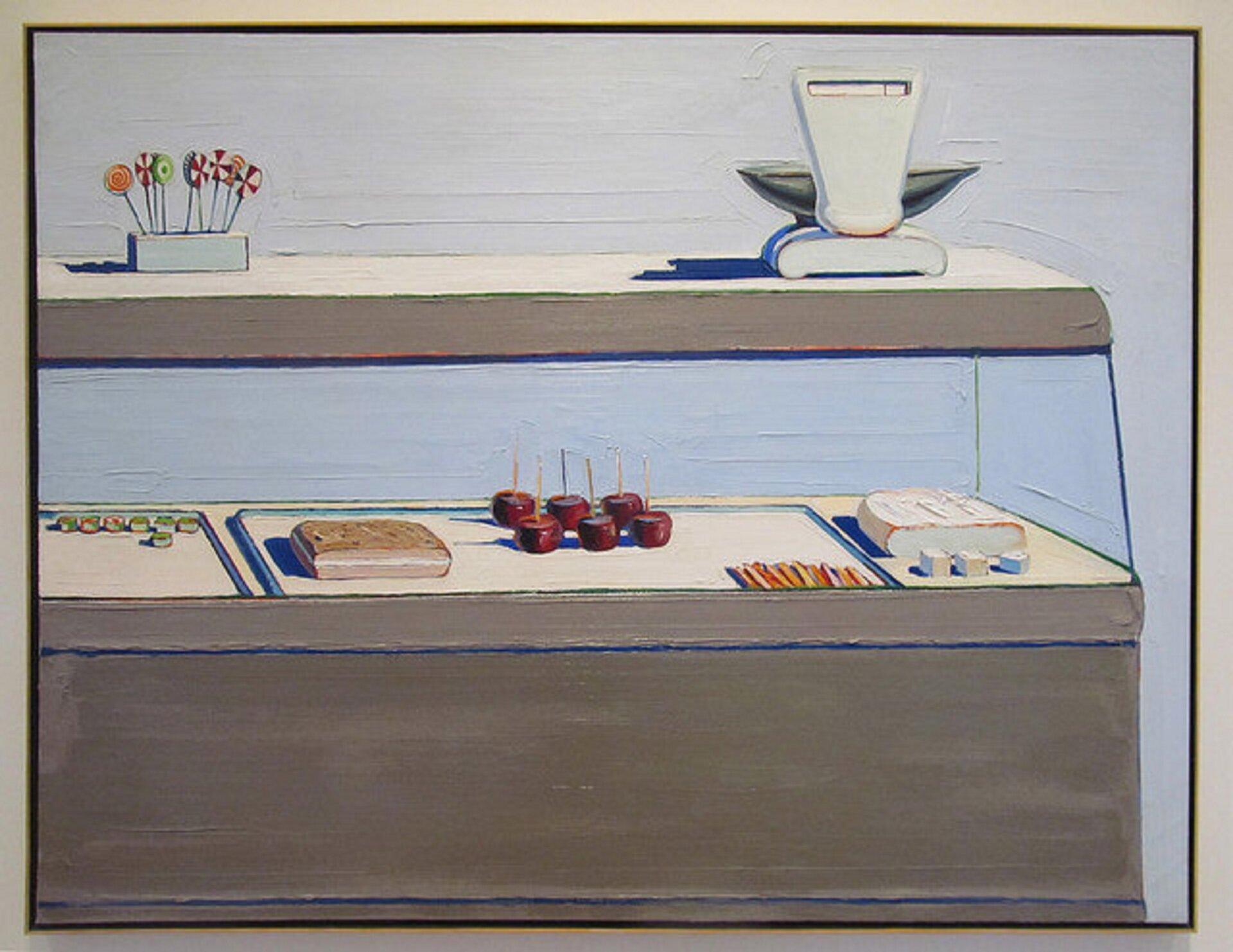 Ilustracja przedstawia ladę sklepową zchłodnią. Za szybą znajdują się praliny oraz ciasta. Na górze stoi waga ilizaki. Tłem jest szarawa ściana.
