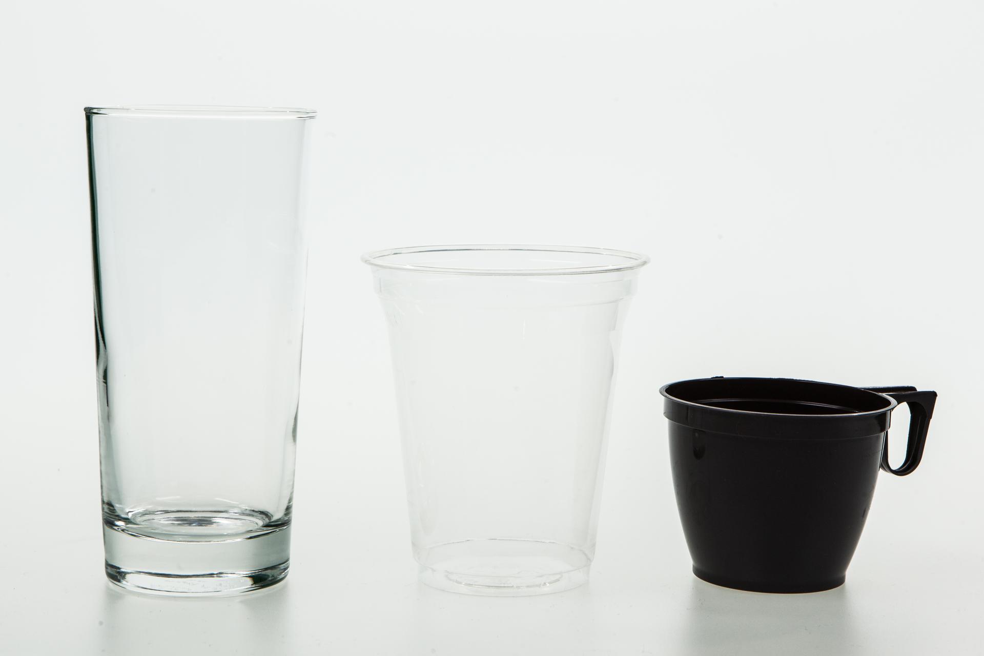 Fotografia przedstawia trzy różne naczynia: szklankę idwa plastikowe kubki jednorazowe.