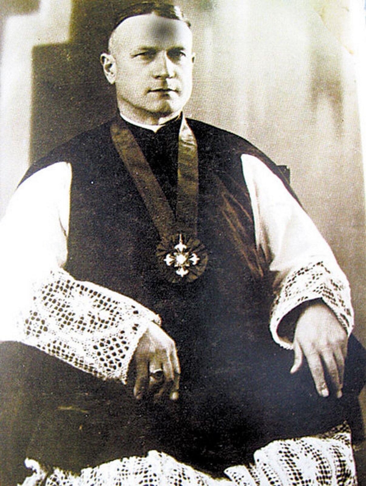 Fotografia nieznanego autora przedstawia portret Władysława Skierkowskiego. Mężczyzna ma krótkie włosy ipozuje na siedząco. Ubrany jest wbiałą szatę oraz czarną narzutę.