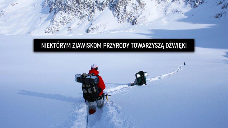 """Ilustracja przedstawia dwóch alpinistów zplecakami schodzącymi ze zbocza ośnieżonej góry. Jest bardzo dużo śniegu. Alpiniście na pierwszym planie śnieg sięga po kolana, aalpiniście, który widoczny jest na drugim planie, śnieg sięga do pasa. Jest słoneczny, mroźny dzień. Ilustracja ma podpis: """"Niektórym zjawiskom przyrody towarzyszą dźwięki""""."""
