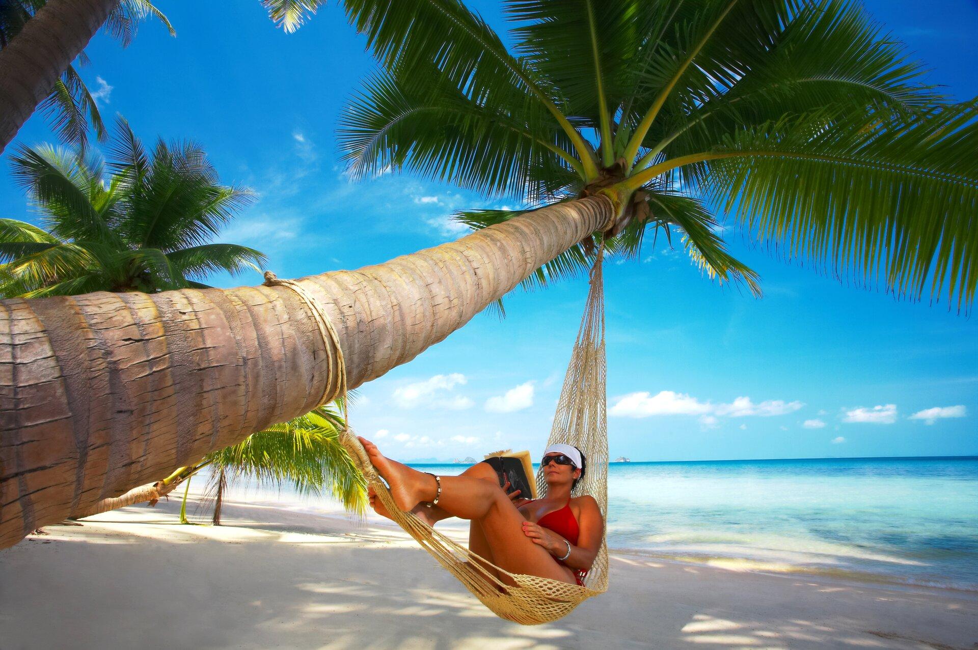 Zdjęcie przedstawia kobietę odpoczywającą na hamaku.