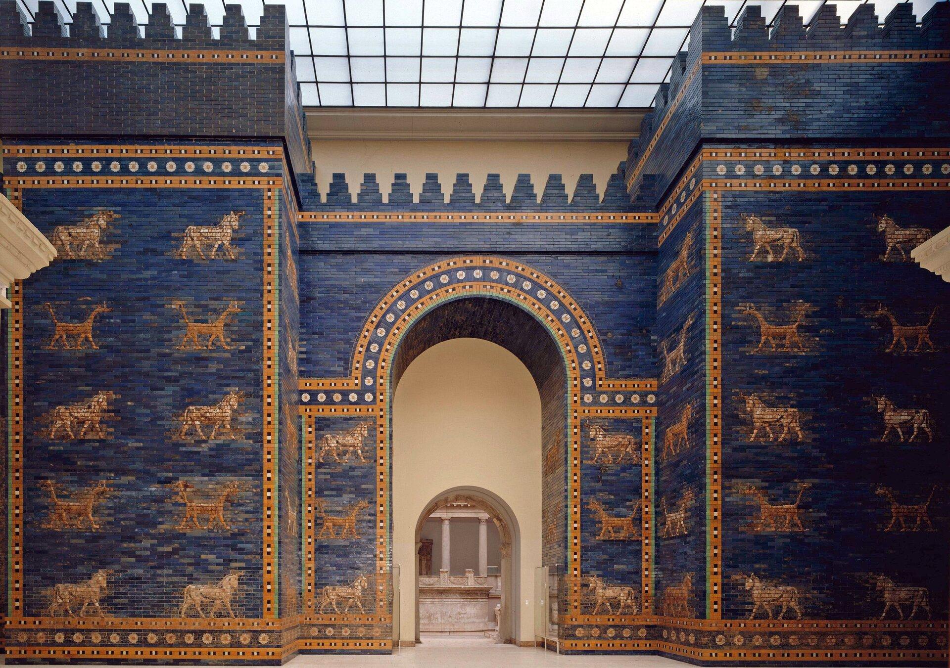 Ilustracja przedstawia Bramę Isztar znajdującą się wMuzeum Pergamońskim wBerlinie. Zdjęcie ukazuje dwie duże, sześcienne wierze, pomiędzy którymi znajduje się wejście zwieńczone łukiem. Całość zamyka ugóry gzyms wykończony blankami – zębatym zwieńczeniem muru. Ściany budowli obłożone zostały glazurowaną cegłą wkolorze niebieskim, na której tle umieszczono reliefowe przedstawienia zwierząt (węże, smoki ibyki) wykonane wkolorach żółci, zieleni, bieli iczerwieni. Dodatkowym elementem zdobniczym są pasy rozetek obramowujących płaszczyzny murów oraz zdobiących sklepienie przejścia.