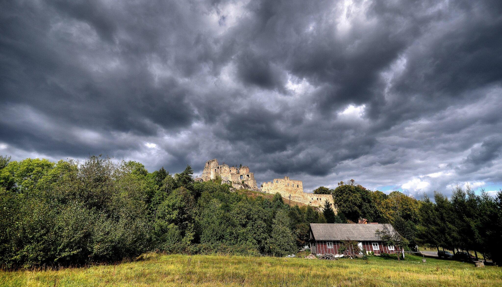 Na niebie ciemne chmury burzowe kłębią się nad ruinami zamku ibaszty stojących na wzgórzu. Wokół wzgórza rosną drzewa, aujego stóp stoi drewniana, brązowa chata, przy której na drodze stoją samochody.