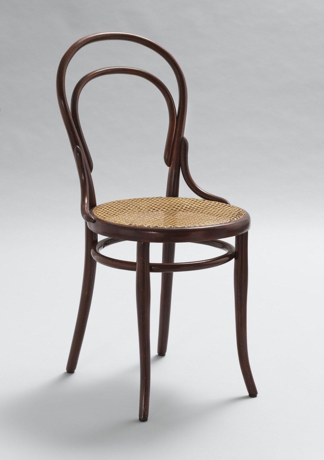 Ilustracja przedstawia krzesło wstylu biedermeier. Krzesło jest brązowe, utrzymane jest wprostym stylu, posiada delikatnie wygięte nóżki oraz sitkowane siedzisko, mebel nie ma cech szczególnych.