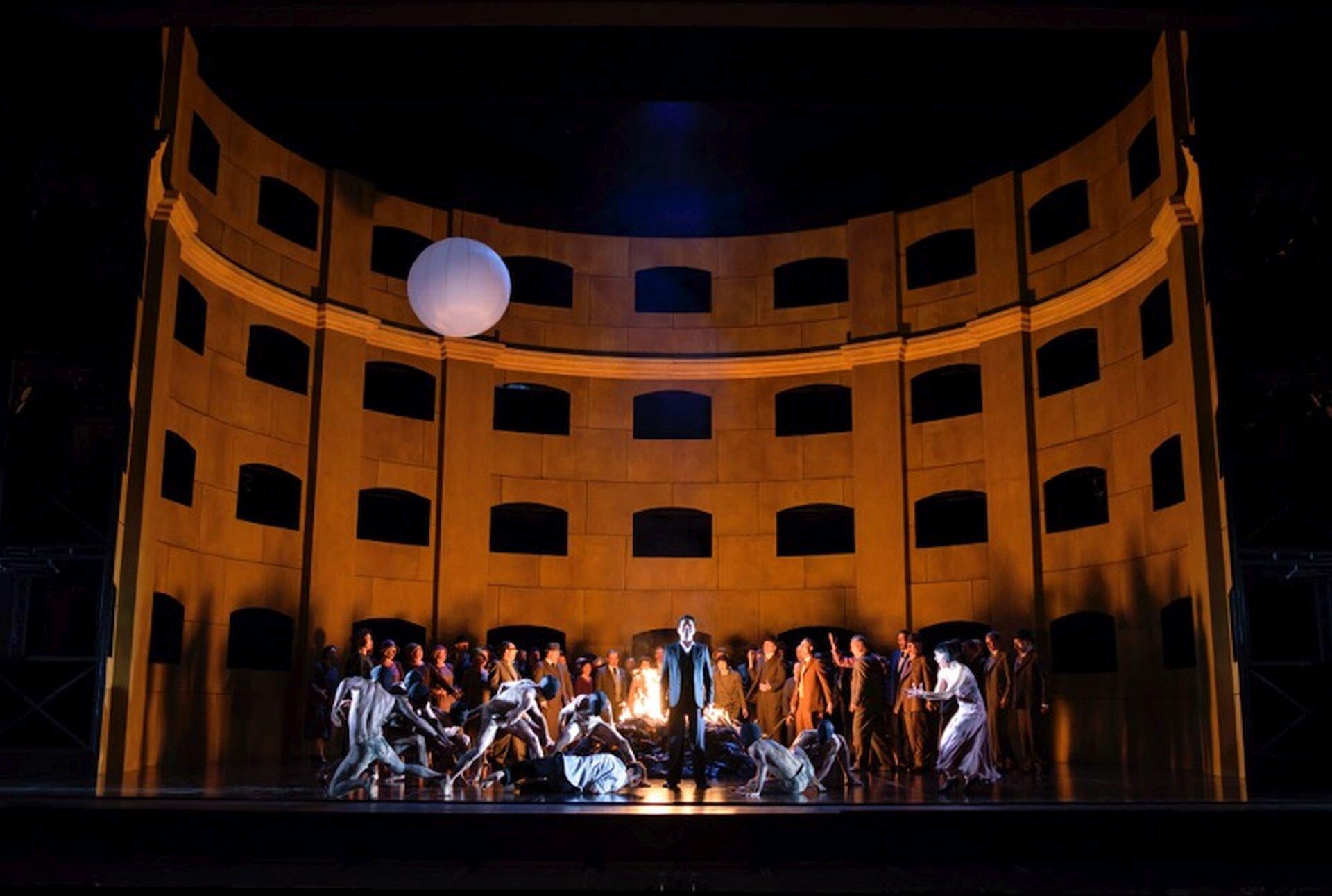 Ilustracja przedstawia operę pt. Król Roger. Autorem jest Karol Szymanowski. Na scenie znajdują się postaci biorące udział wprzedstawieniu. Na środku stoi mężczyzna wmarynarce, który wpatrzony jest wwidownię.