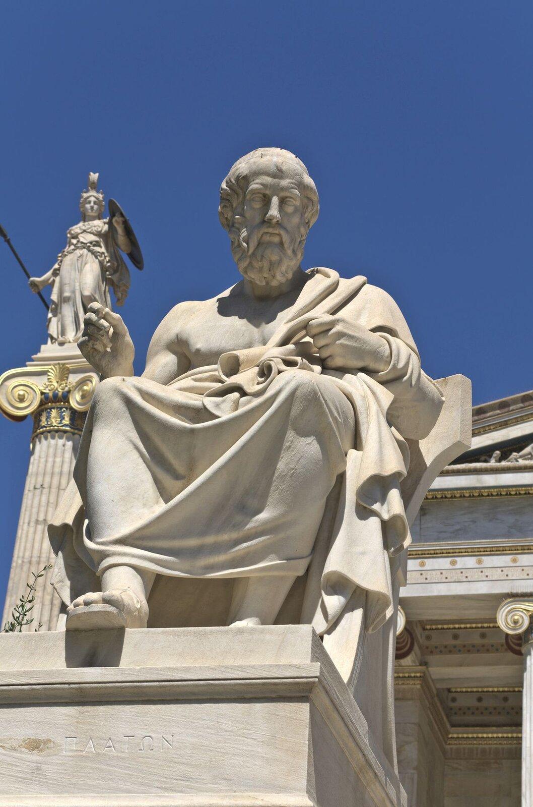 Fotografia nieznanego autora przedstawia posąg Platona. Został on pokazany jako mężczyzna wpodeszłym wieku. Siedzi wtodze trzymając zwój papirusu.