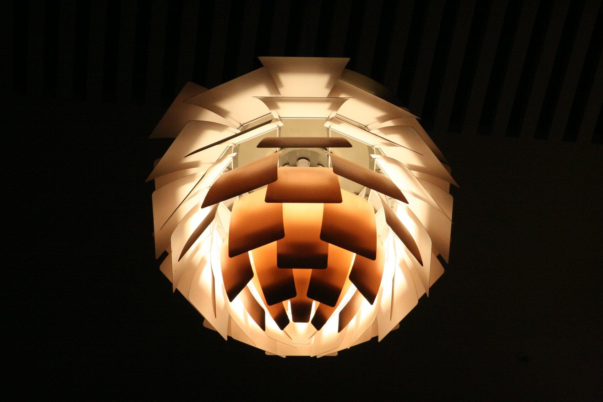 Ilustracja interaktywna przedstawia lampę typu PH Artichoke zaprojektowaną przez Poula Henningsena. Lampa przypomina rozwarstwioną kulę, składa się ona zwielu kwadratowych elementów, które wcałości prezentują lampę okulistym kształcie.