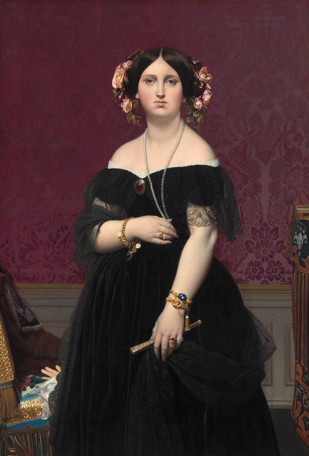 """Ilustracja przedstawia obraz olejny """"Portret Madame Moitessier"""" autorstwa Jeana-Augustea-Dominiquea Ingresa. Dzieło ukazuje damę wczarnej, koronkowej sukni zczerwoną broszką iodkrytymi ramionami. Spoglądająca zobrazu kobieta, ma ciemne, gładkie włosy zprzedziałkiem pośrodku czoła, spięte do tyłu. Zdobią je różowe kwiaty. Zszyi zwisa sznur pereł. Ręce zdobią złote bransolety. Wlewej, opuszczonej wzdłuż tułowia dłoni trzyma wachlarz. Prawa spoczywa na talii sukni. Postać ustawiona jest wpokoju, na tle ściany obitej ciemno-różową tkaniną ozdobioną kwiatowymi ornamentami. Wgłębi obrazu, artysta namalował również wystające zza kadru fragmenty mebli. Obraz skomponowany jest statycznie, postać kobiety znajduje się wjego centrum."""