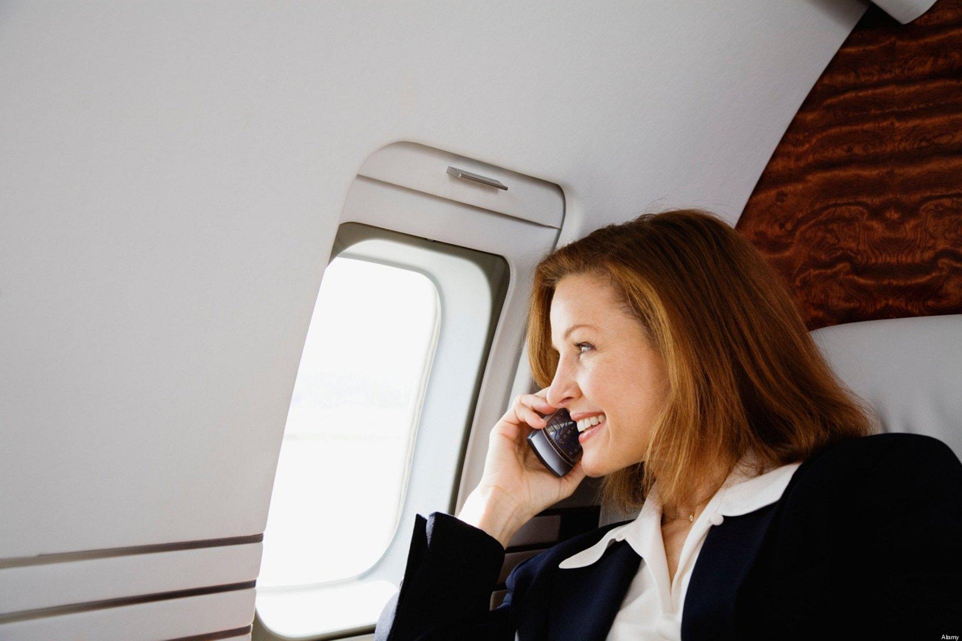 Zdjęcie przedstawia kobietę weleganckim stroju biznesowym siedzącą wfotelu przy oknie wprywatnym samolocie. Spogląda przez okno rozmawiając przez telefon iuśmiecha się.