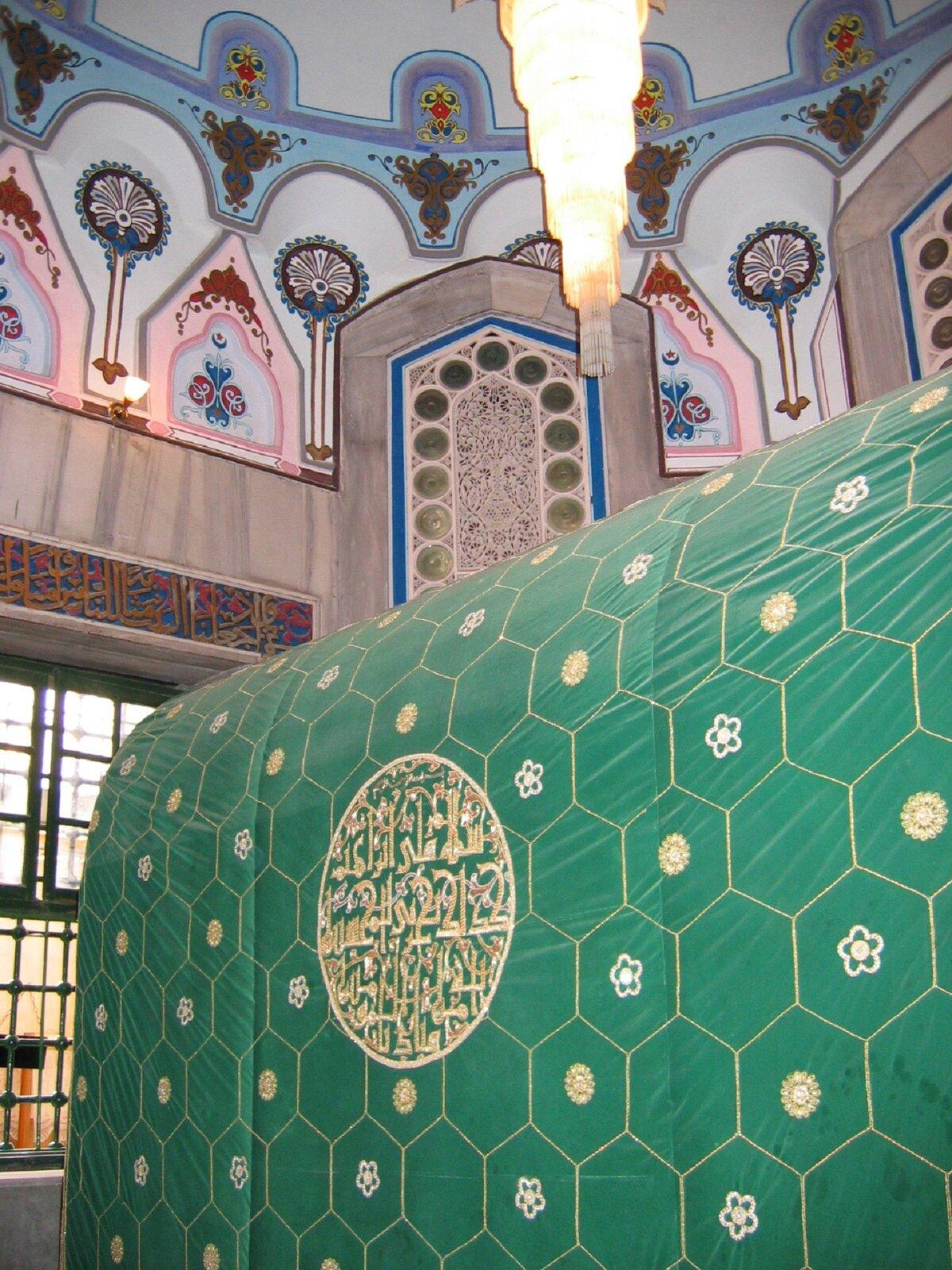 Ilustracja przedstawia Grób Abrahama. Grafika ukazuje liczne kolorowe zdobienia ścian oraz długi wiszący żyrandol. Na głównym planie widoczne jest zielone, zdobione złotymi wzorami płótno.