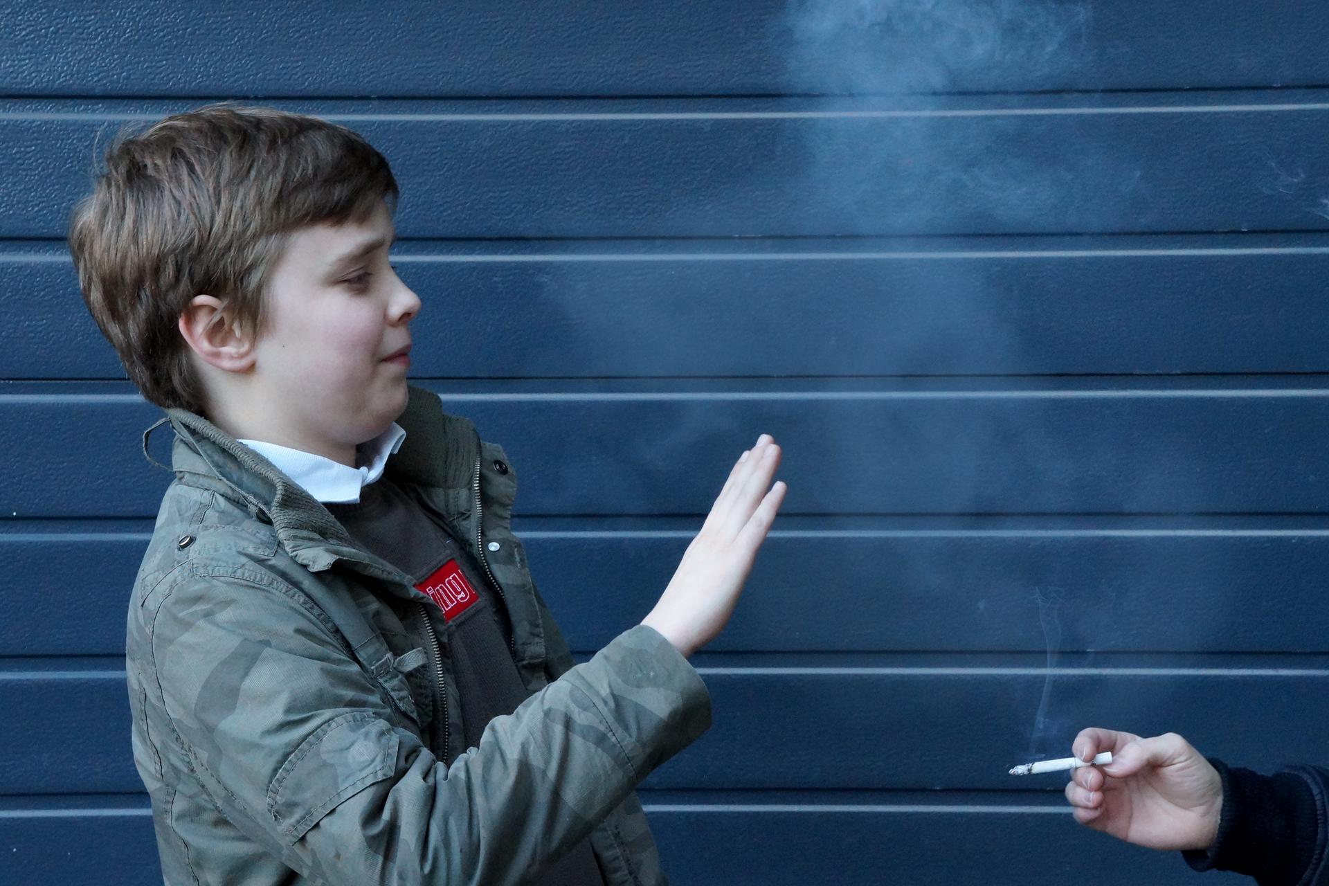 Fotografia przedstawiająca postać młodego człowieka oraz dym papierosowy