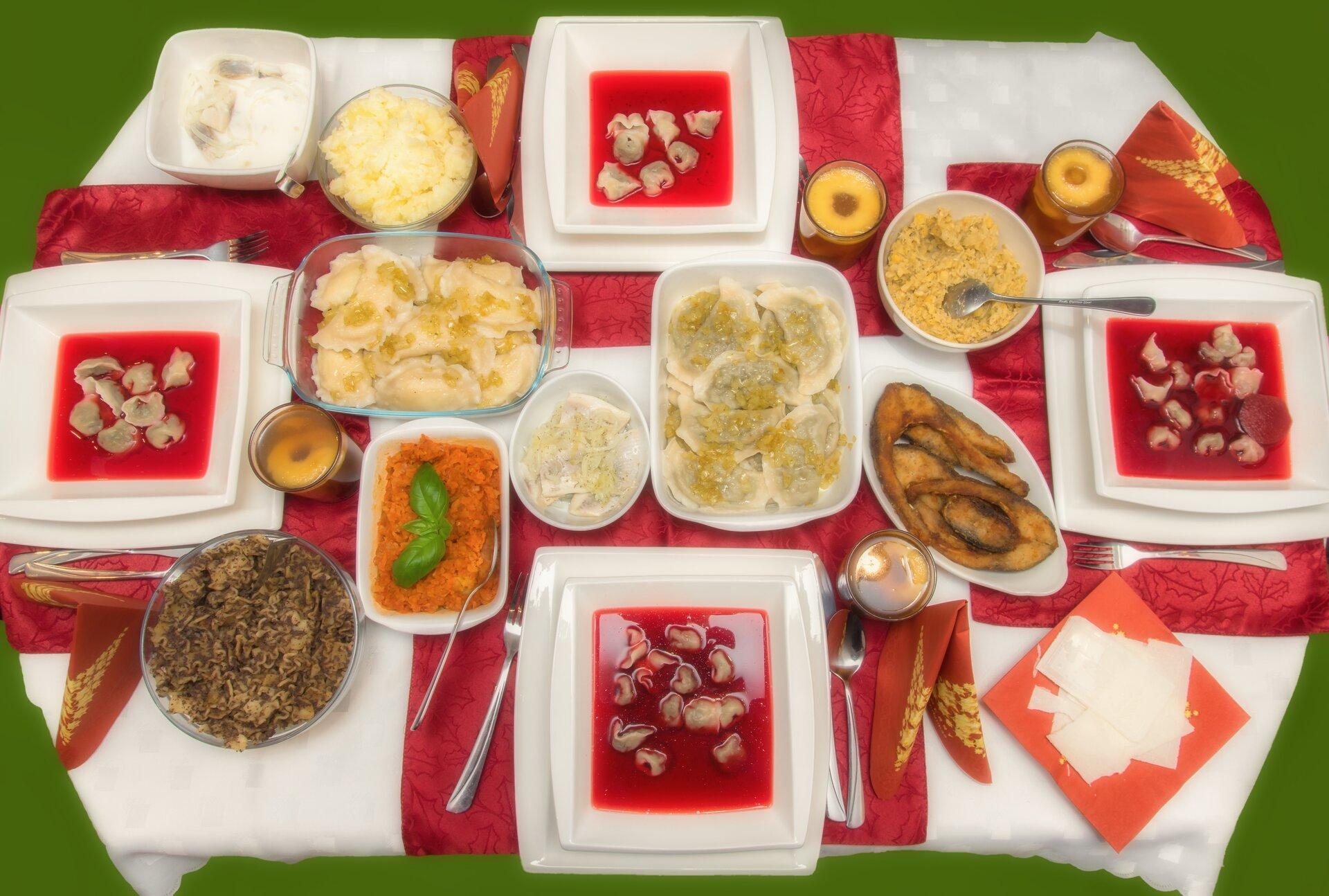 Ilustracja przedstawia stół wigilijny. Na stole znajdują się pełne talerze zczerwonym barszczem iuszkami. Wpółmiskach znajdują się dania wigilijne takie jak: kutię, rybę po grecku, karp, pierogi, kompot, śledzie.