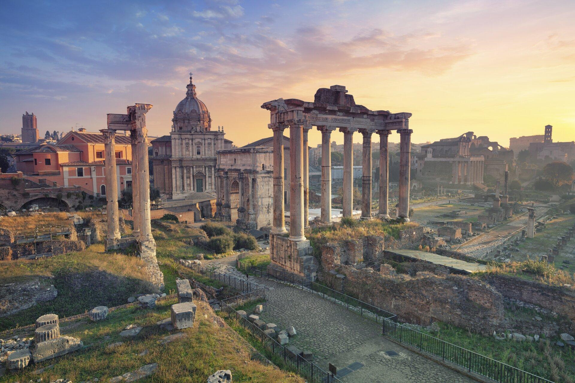 Fotografia przedstawia widok współczesny na Forum Romanum – ruiny jednego zważniejszych miejsc dla starożytnego Rzymu. Fotografia została wykonana zoddali. Wcentrum znajdują się pozostałości po kompleksie budynków – głównie są to kolumny oraz fundamenty. Pomiędzy ruinami budynków widoczne są tereny zielone. Na drugim planie znajdują się nowożytne budowle. Fotografia została wykonana wlekko zachmurzony dzień.