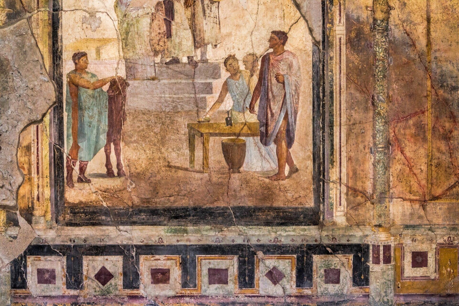 Kolorowa ilustracja przedstawia fresk ztzw. Domu Złotych Kupidynów wPompejach. Ukazane jest wnętrze pomieszczenia. Po prawej stronie znajduje się niewysoki stół, przy którym stoi troje ludzi. Na pierwszym planie ukazany jest mężczyzna wprostej szacie sięgającej za kolana. Przygląda się drugiemu, stojącemu wlewej części obrazu. Tamten, ubrany wzwiewną zielononiebieską szatę, trzyma przed sobą wysoki płaski przedmiot stojący na dwóch nogach; być może jest to instrument muzyczny. Wtle obrazu znajdują się schody prowadzące do wnętrza mieszkania. Fresk wdolnej części udekorowany jest motywem meandrycznym, zaś po jego prawej stronie znajduje się namalowana ozdobna kolumna. Lewa strona fresku uległa zniszczeniu.