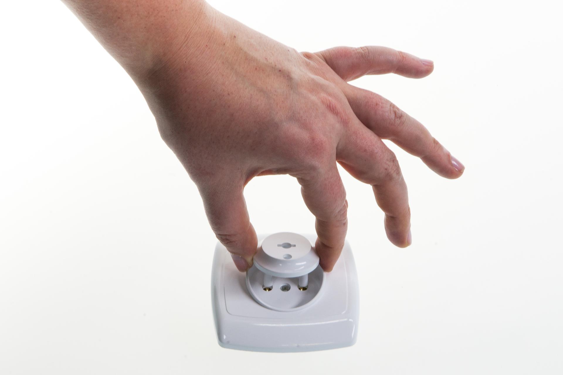 Fotografia przedstawia rękę człowieka umieszczającego zaślepkę wgniazdku elektrycznym.