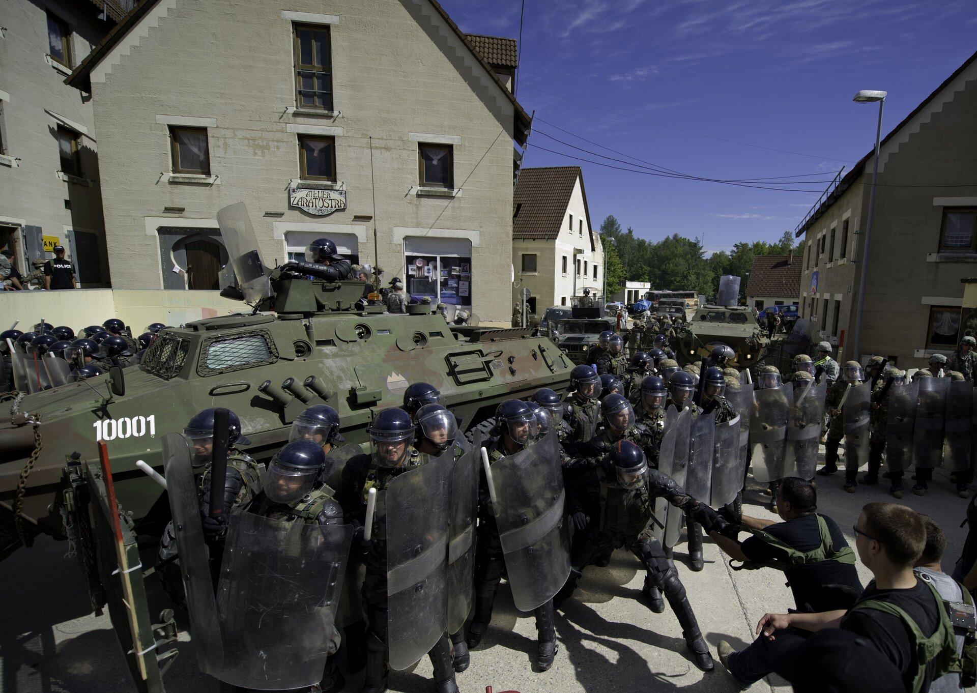 Na zdjęciu żołnierze wpełnym umundurowaniu wkaskach zmaskami. Trzymają przezroczyste tarcze. Ztyłu pojazd pancerny wkolorze zielonym zbrązowymi plamami. Wtle domy isklepy.