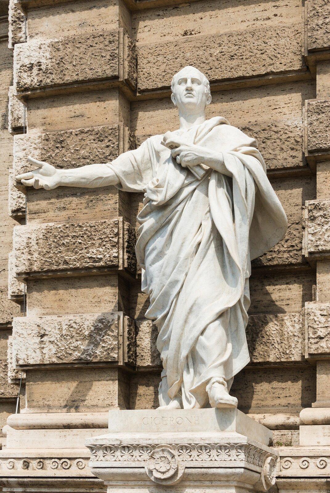 Ilustracja przedstawia pomnik Cycerona jako prawnika. Jest on wykonany zjasnego kamienia, stoi na tle kamiennej ściany. Mężczyzna odziany jest wdługie szaty. Głowę ma lekko uniesioną do góry. Jest łysy, jedynie nad uszami widnieją ślady włosów. Prawą rękę wyciągniętą ma przed siebie, wlewej przyciska do piersi zwój papirusu. Wyciągnięta lewa stopa sugeruje ruch. Posąg ustawiony jest na postumencie, na którym widnieje napis CICERONE.