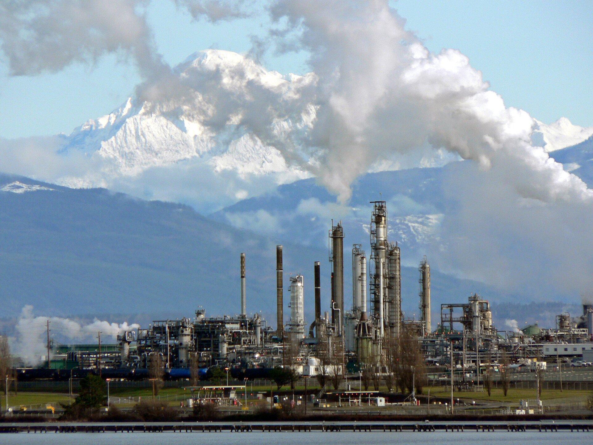 Na zdjęciu na pierwszym planie zbiornik wodny. Dalej na brzegu wielka rafineria ropy naftowej, rury, kominy, instalacje do rafinacji ropy. Wtle wysokie góry. Najwyższe partie gór pokryte śniegiem.