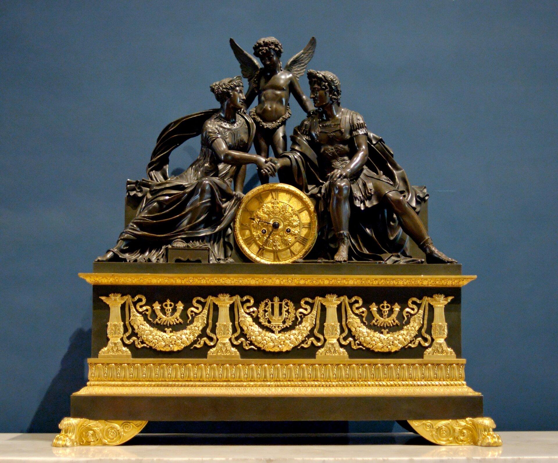 Ilustracja przedstawia zegar wfrancuskim stylu Empire. Przez zegar dominuje złoto ibrąz. Na centralnym miejscu widać trzy postacie kobiete imężczyzne wtz. uścisku dłoni oraz anioła stojącego nad nimi, opierającego swoje dłonie na ramieniu kobiety imęzczyzny. Zegar jest bogato zdobiony.