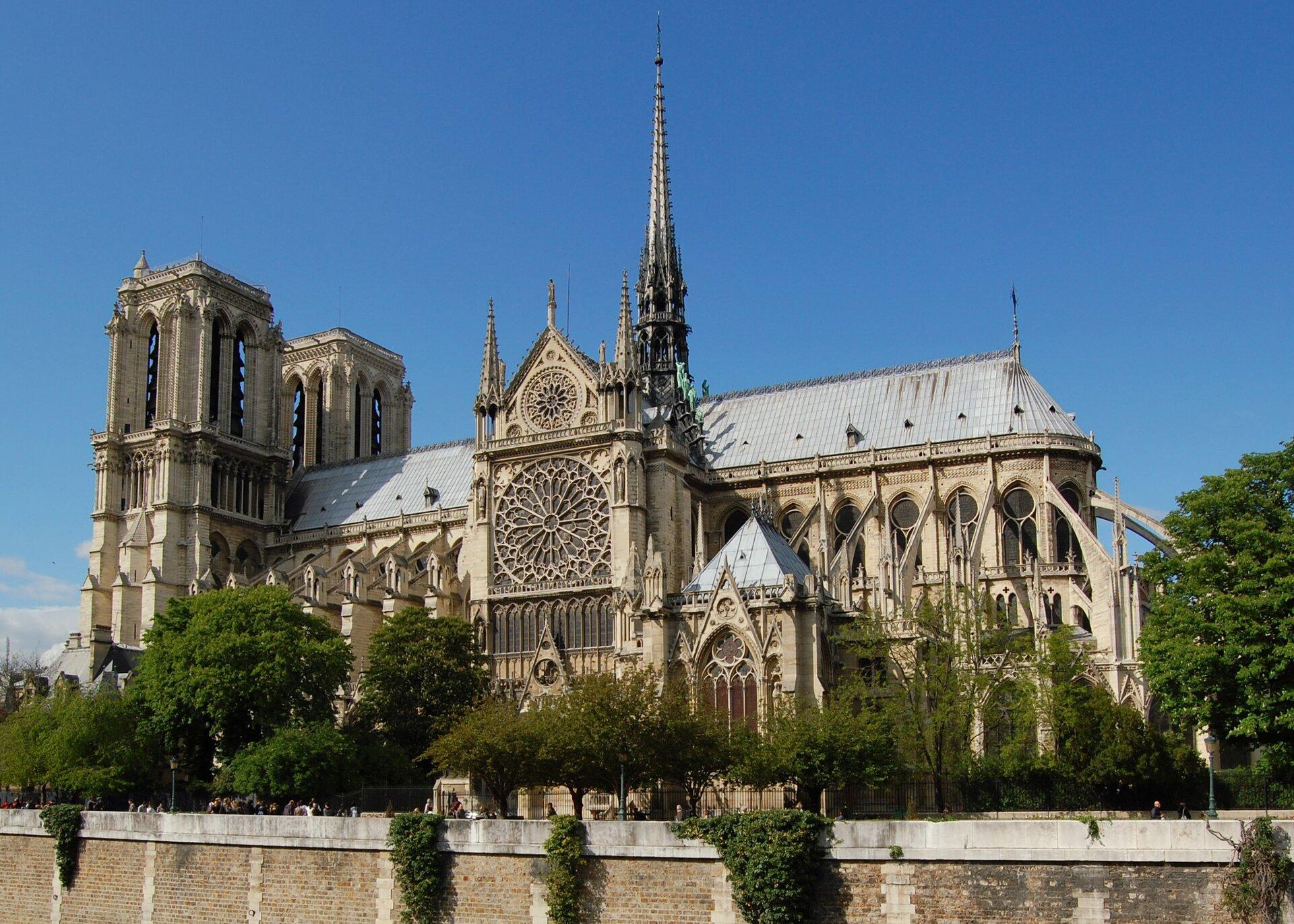 Na zdjęciu gotycka katedra. Widok zboku. Zlewej strony dwie wieże, na środku strzelista wieża. Piaskowe mury, szary dach, rozety iwitraże. Dookoła katedry drzewa.