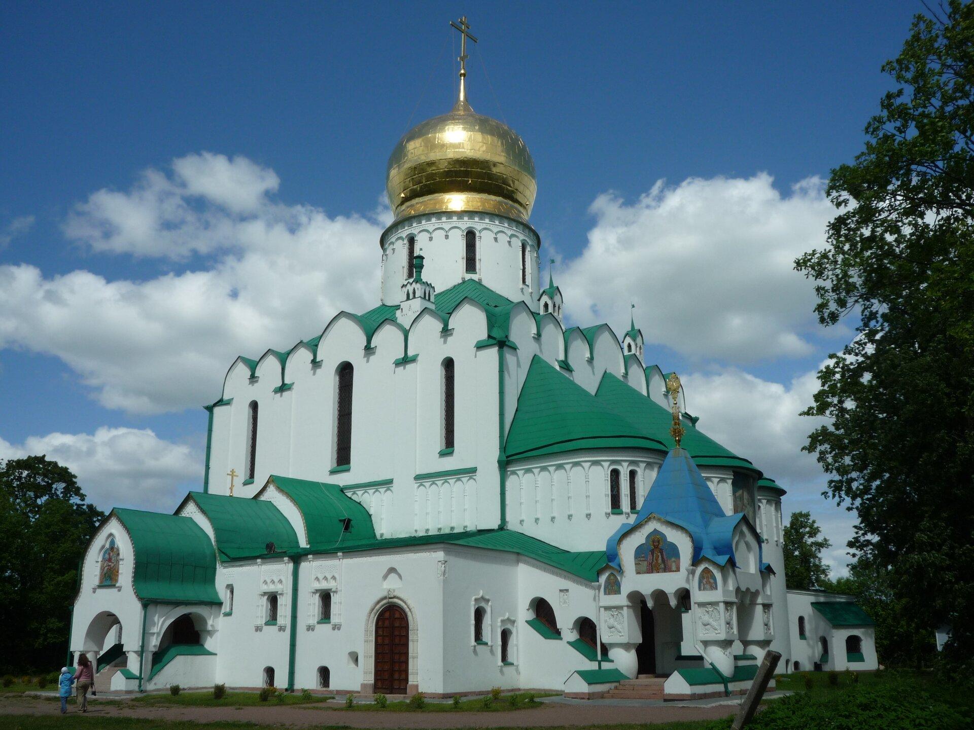 Na zdjęciu cerkiew prawosławna, biały budynek orozbudowanej bryle, dach zielony, jeden daszek niebieski, złota kopuła na wieży.