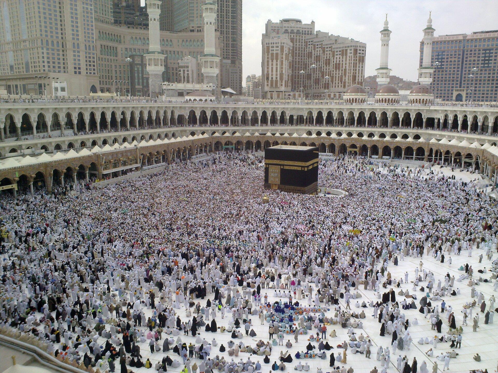 Zdjęcie przedstawia dziedziniec wkształcie wieloboku otoczony kilkupiętrowymi krużgankami. Na środku dziedzińca wielki sześcian wciemnym kolorze. To Al-Kaba, świątynia isanktuarium wMekce, najważniejsze miejsce święte islamu. Wokół świątyni tłumy wiernych.