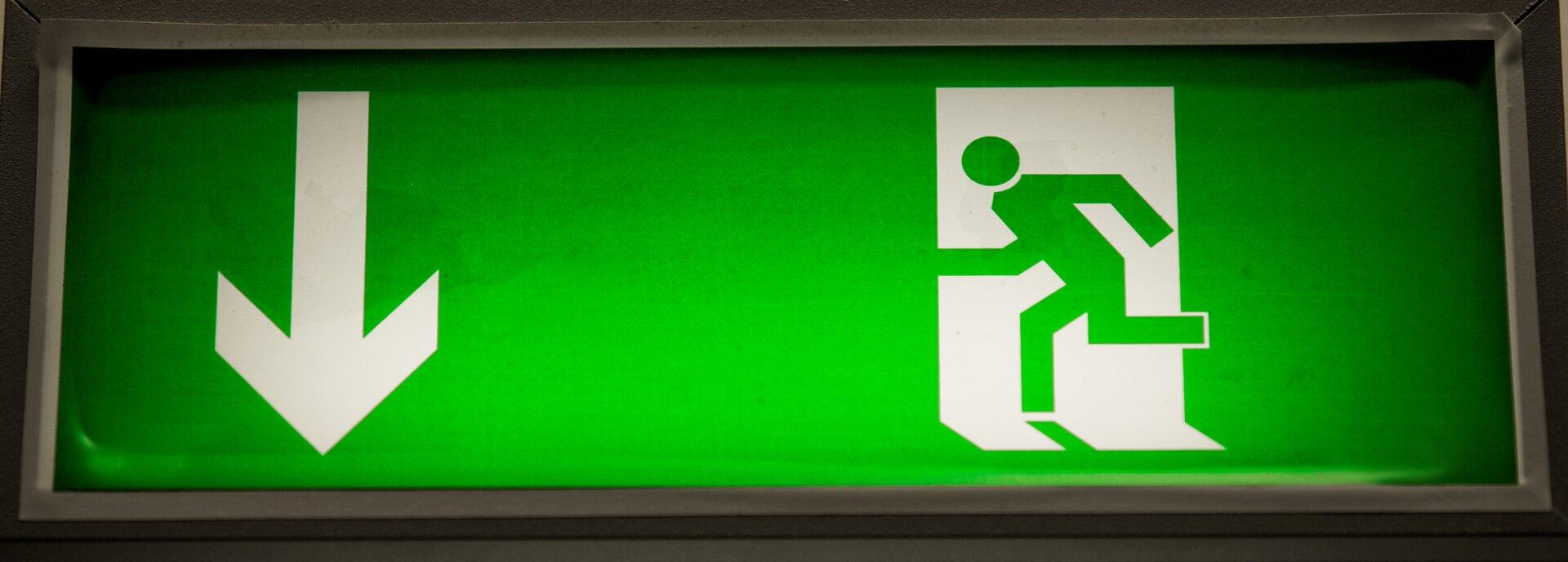 Na zielonym intensywnym tle przedstawiony jest symbol uciekającego człowieka – obok niego, po lewej stronie, strzałka skierowana wdół, informująca okierunku ewakuacji.