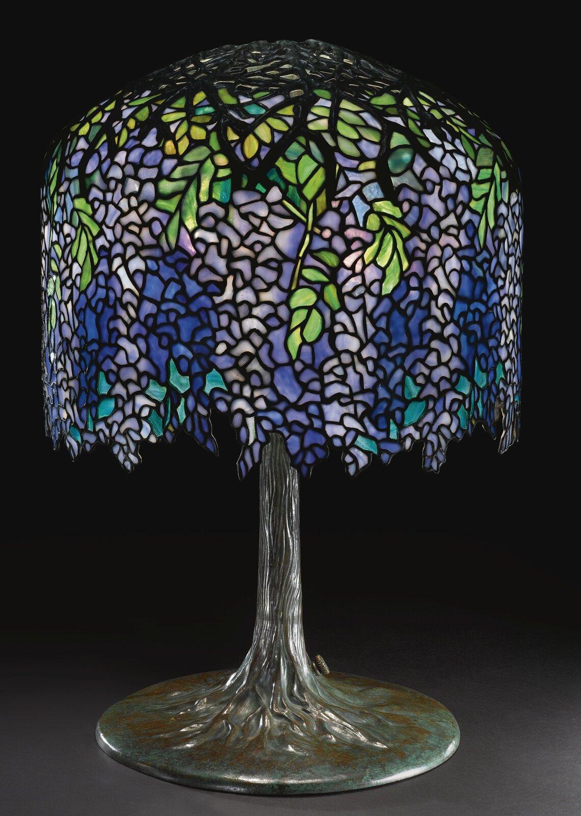 Ilustracja przedstawia lampkę stołową, której klosz złudząco przypomina witraż zwinogronami. Lampka stanowi funkcjonalny oraz jednocześnie ozdobny przedmiot.