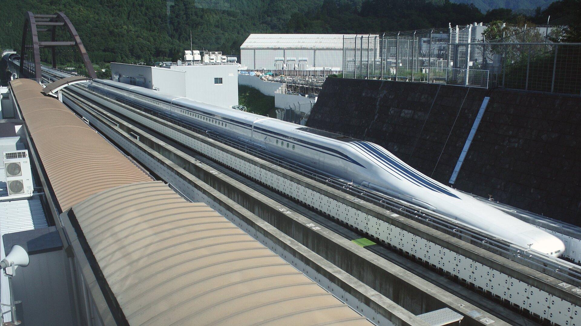 Zdjęcie przedstawia japoński pociąg magnetyczny składający się zpięciu wagonów tworzących niemal jednolity kształt. Pociąg jest biały zciemnoniebieskimi pasami. Pierwszy wagon jest niemal dwukrotnie dłuższy od pozostałych, ajego pierwsza połowa zwęża się ku dołowi tworząc opływowy kształt. Zdjęcie wykonano podczas testów, pociąg został uwieczniony na torach, sfotografowany nieco zprzodu, zboku izgóry. Wtle widoczne budynki przemysłowe imost kolejowy.