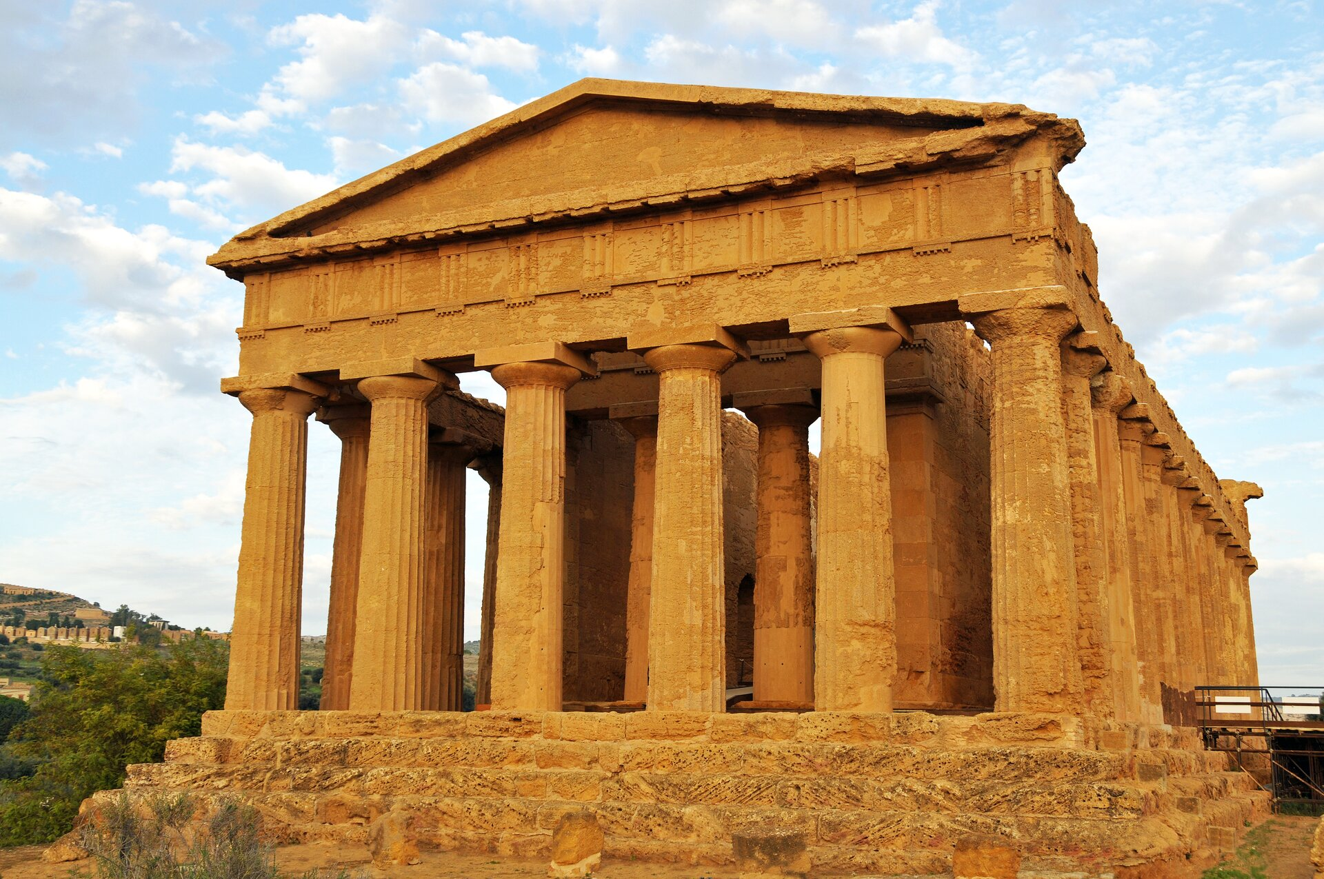 """Ilustracja przedstawia fotografię """"Świątyni Concordii"""". Fotografia ukazuje budynek Świątyni Concordii znajdującej się wDolinie Świątyń, wAgrigento, na Sycylii, we Włoszech. Budynek składa się zwielu wysokich, pionowych filarów podpierających pozostałości dachu świątyni."""