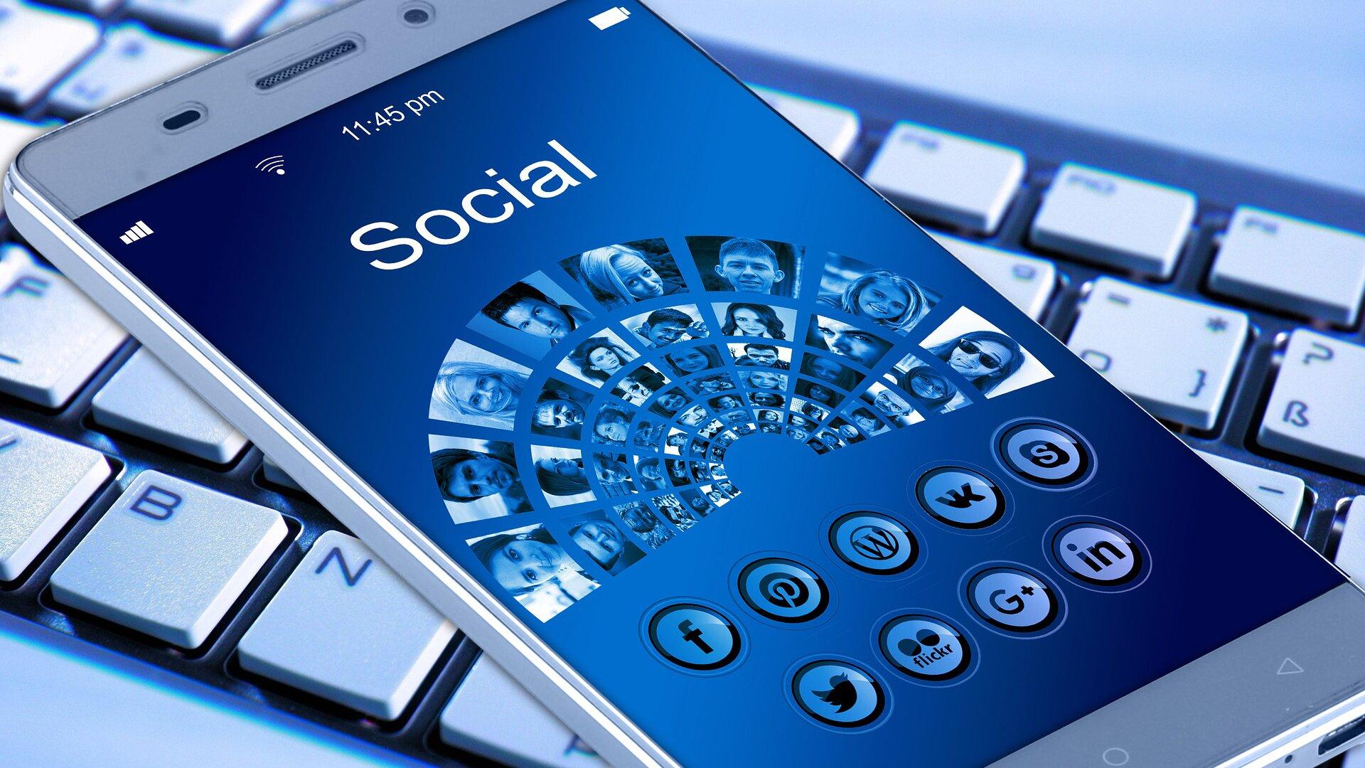 """Zdjęcie przedstawia leżący na klawiaturze komputera smartfon. Na jego ekranie widać otwartą stronę mediów społecznościowych zdużym napisem """"Social"""" oraz ze zdjęciami ludzkich twarzy ułożonych na ekranie półkoliście. Na dole ekranu widać przyciski do nawigacji."""