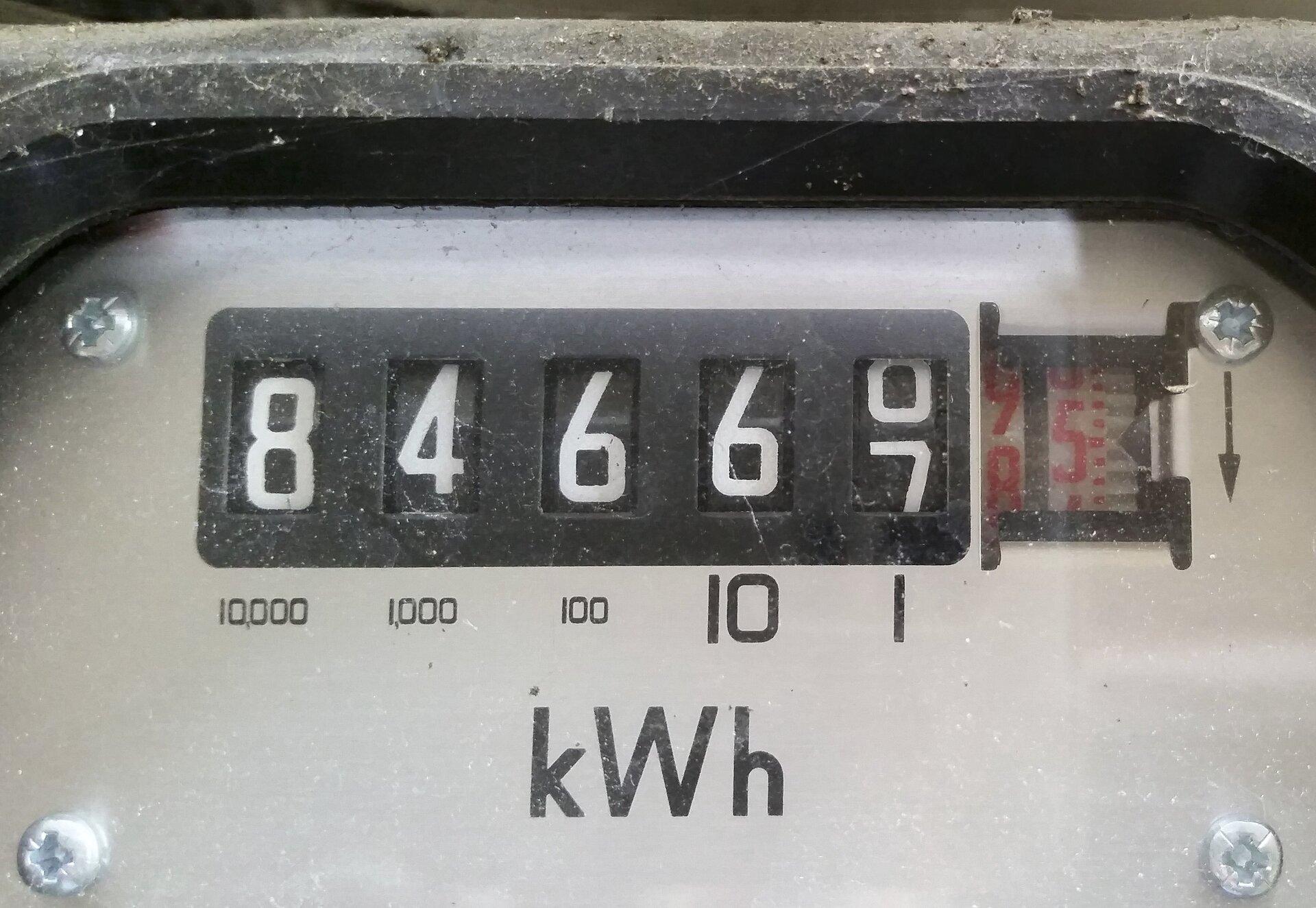 Zdjęcie przedstawia zbliżenie fragmentu przedniego panelu licznika energii elektrycznej, adokładniej tarczę licznika wskazującą wartość 84667,5 oraz symbol jednostki kWh poniżej.