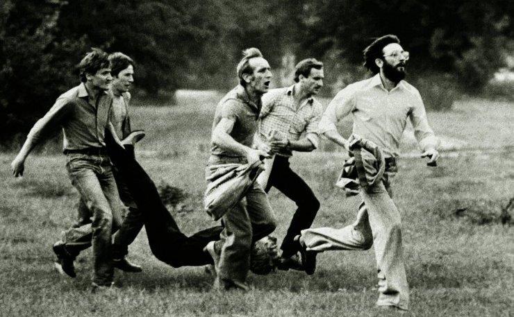 Zdjecie przedstawia jedno znajsłynniejszychzdjęć okresu stanu wojennego, na zdjeciu czterech mężczyzn, biegnącniesie rannego człowieka.