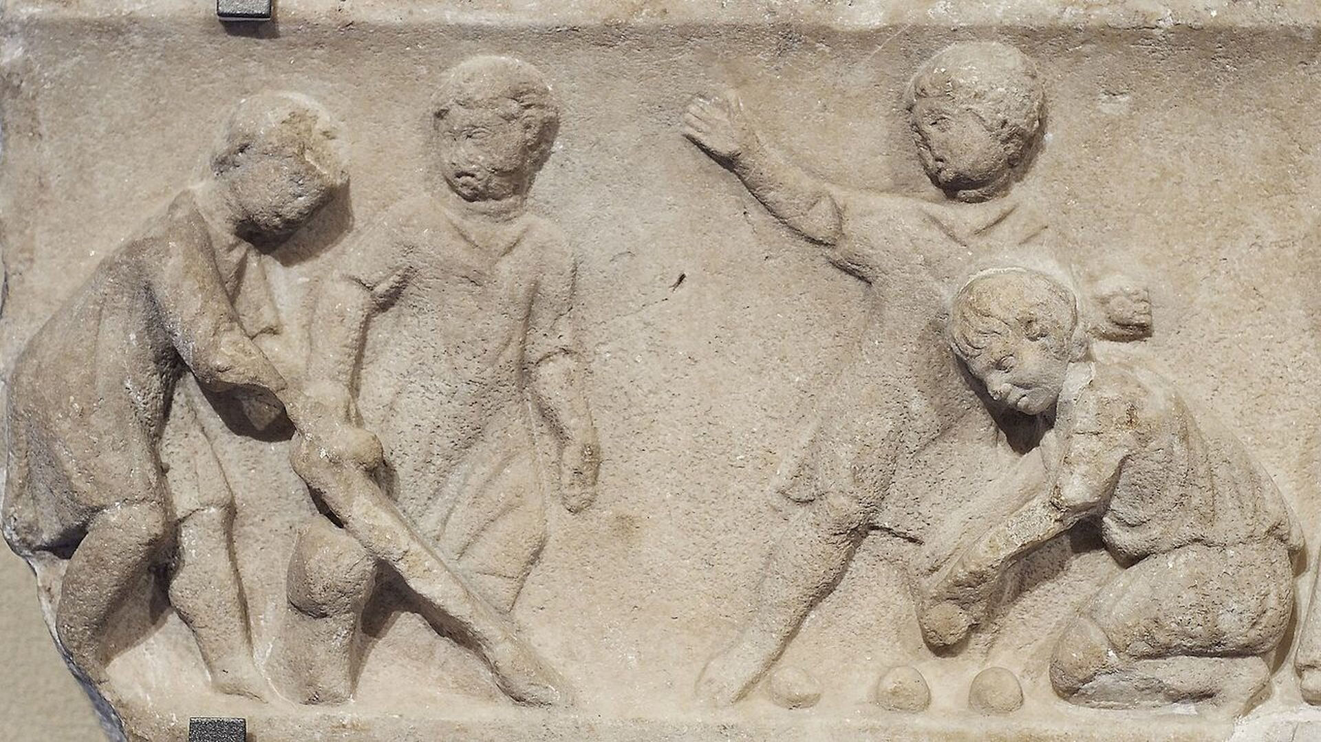 Relief nieznanego autora przedstawia czworo chłopców grających wpiłkę. Trzech znich stoi, jeden klęczy iukłada piłki na ziemi. Płaskorzeźba została wykonana na ścianie budynku.