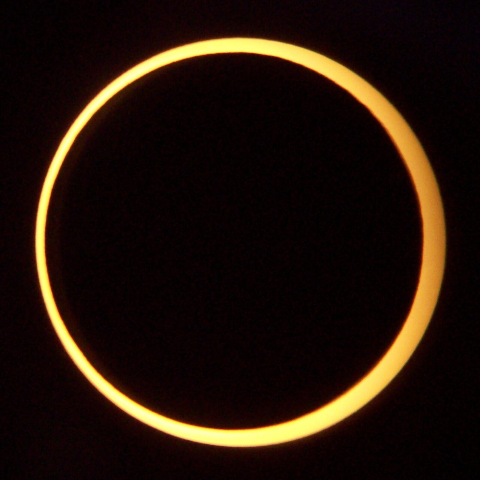 Zdjęcie przedstawia pierścieniowe zaćmienie Słońca. Tarcza Słońca zakryta jest tarczą Księżyca, który znajduje się pomiędzy Słońcem iZiemią. Wokół ciemnej tarczy Księżyca znajduje się ognisty żółty pierścień tarczy Słońca, gdyż tarcza Słońca jest większa od tarczy Księżyca. Na zdjęciu tło czarne.