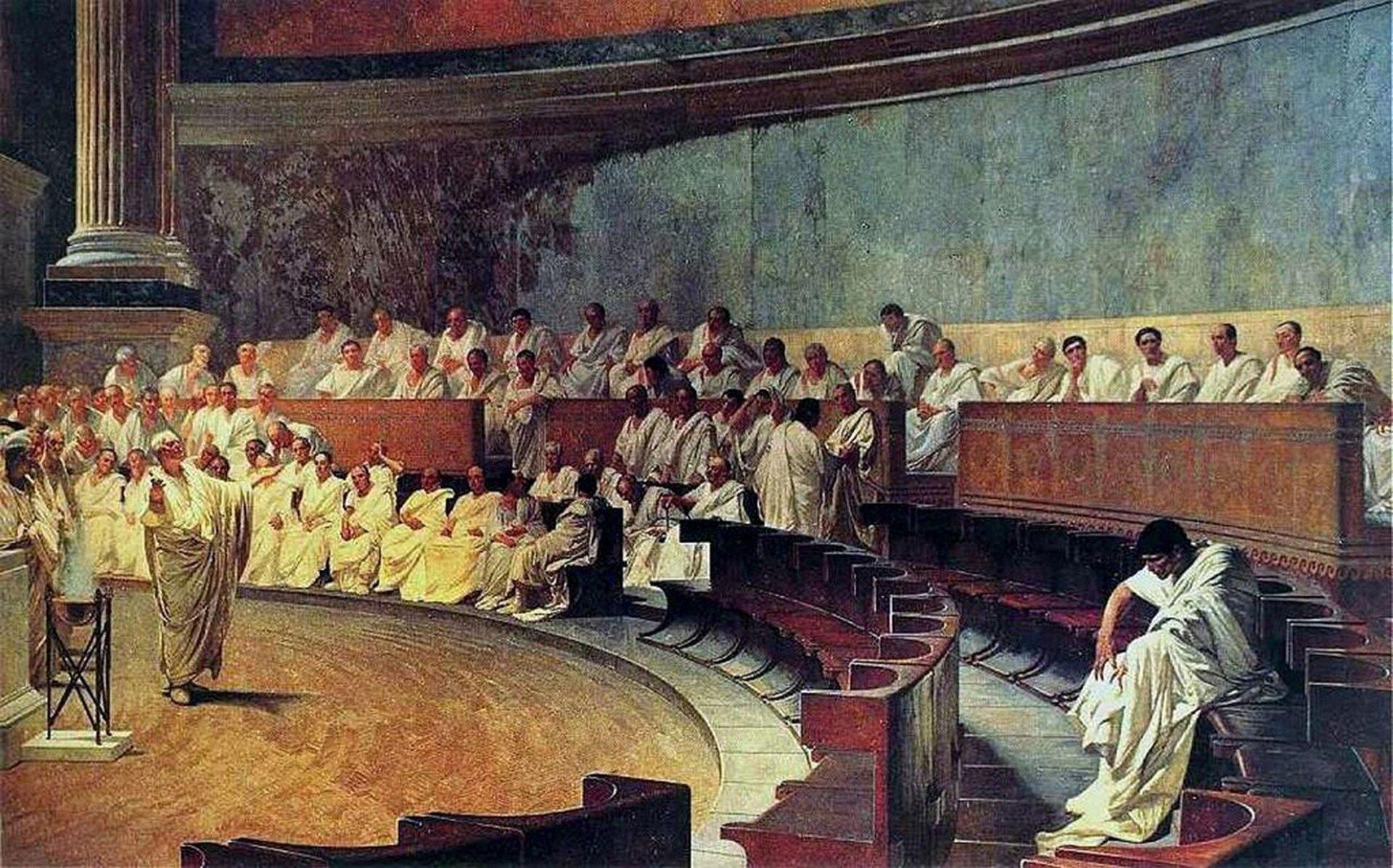"""Kolorowa ilustracja przedstawia dzieło Cesare Maccari'ego pt. """"Cyceron oskarża Katylinę"""". Na obrazie przedstawione jest pomieszczenie sądu. Po prawej stronie, wławach zasiadają senatorowie odziani wbiałe togi. Po lewej, przed słuchaczami stoi Cyceron zrękami wzniesionym wgórę. Ma krótkie siwe włosy, jest ubrany wdługą togę. Wtle, pod ścianą, stoi na postumencie marmurowa kolumna."""