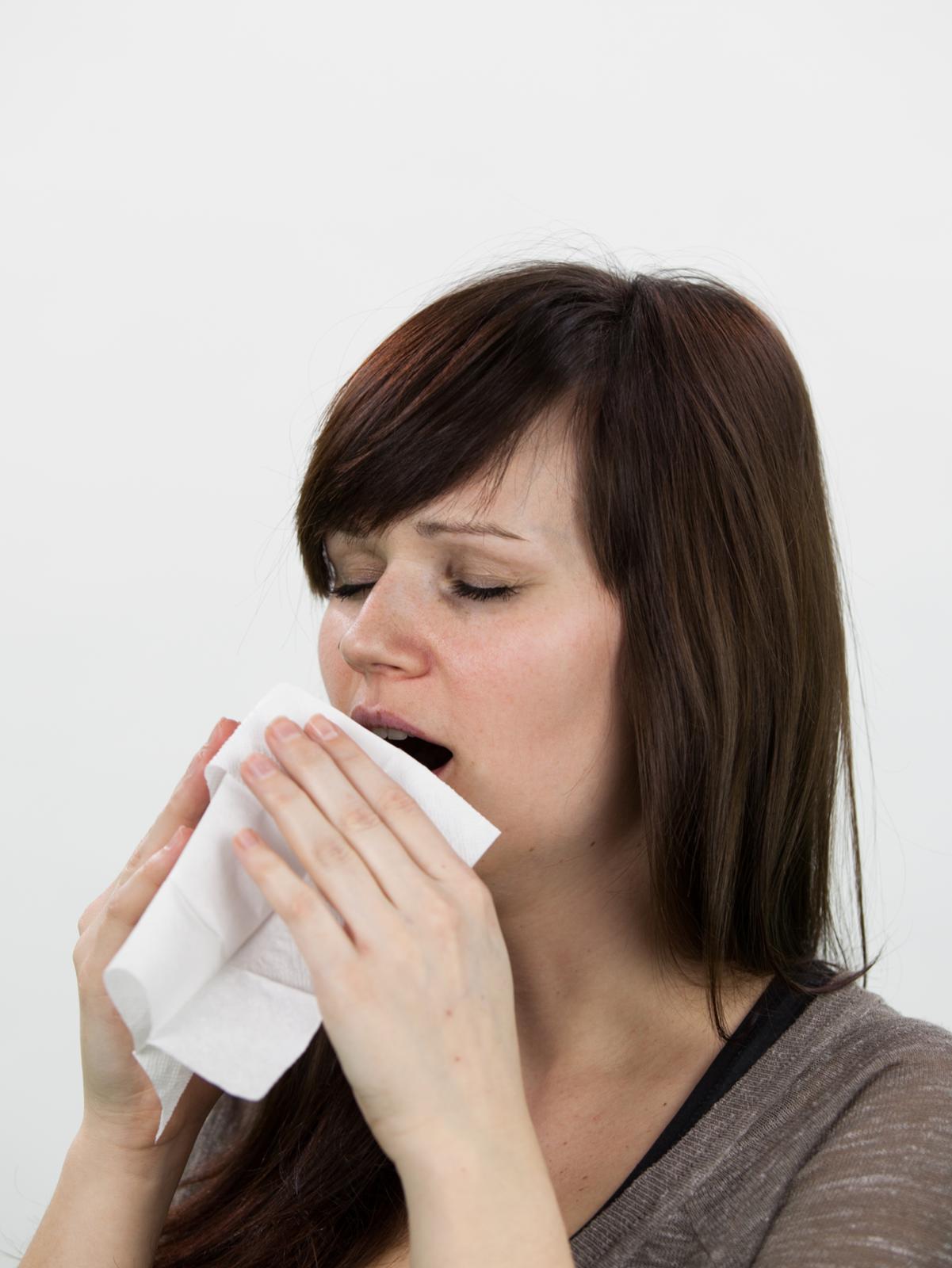 Zdjęcie przedstawia kichającą kobietę. Twarz zwrócona wlewo, oczy zamknięte, otwarte usta częściowo przysłonięte chusteczką trzymaną wrękach. Uchwycony moment na ułamek sekundy przed samym kichnięciem.