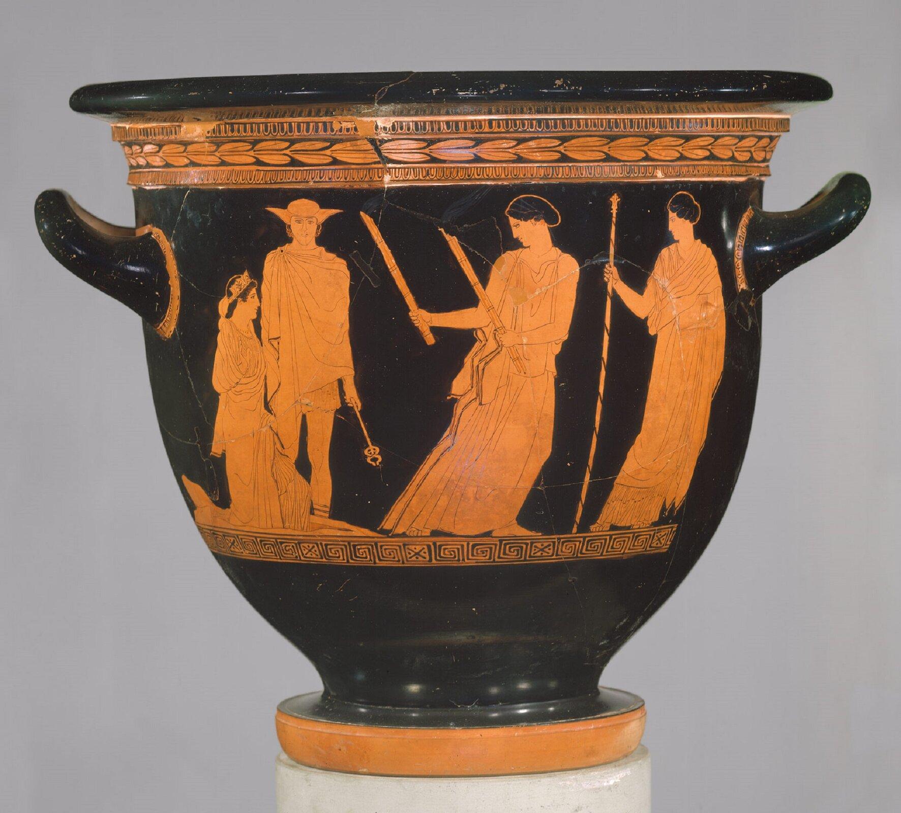 """Fotografia przedstawia naczynie autorstwa malarza Persefony pt. """"Terakotowy krater dzwonowy"""", na którym znajduje się malarstwo czerwonofigurowe. Czarne naczynie posiada pomarańczową podstawkę, czarne ścianki zwystającymi uszami, oraz czarną pokrywę. Na ścianach naczynia znajduje się malunek przedstawiający grupę postaci. Od lewej strony: młoda klęcząca kobieta, ubrana wdługą szatę ztiarą na głowie. Po jej lewej stronie widoczny jest mężczyzna ubrany wczapkę zodstającymi uszami oraz wszatę (jej długość sięga do kolan), wręku trzyma przedmiot podobny do buławy. Zprawej strony widoczne są dwie kobiety – obie są ubrane wdługie szaty itrzymają wdłoniach przedmioty – jedna trzyma dwie ostro zakończone tyczki, druga zaś włócznię. Zdjęcie zostało wykonane na szarym tle."""