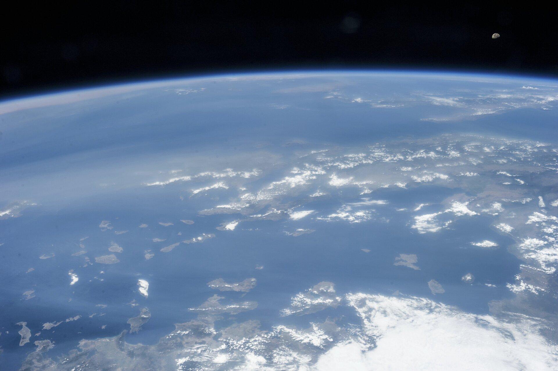 Zdjęcie przedstawia fragment powierzchni Ziemi sfotografowany zorbity. Wcentralnej idolnej części kadru obszar mórz poprzecinanych skrawkami lądu, wczęści górnej zakrzywiona linia horyzontu zniebieskim paskiem atmosfery nad którą rozpościera się czerń kosmosu. Wprawym górnym rogu kadru mały Księżyc.