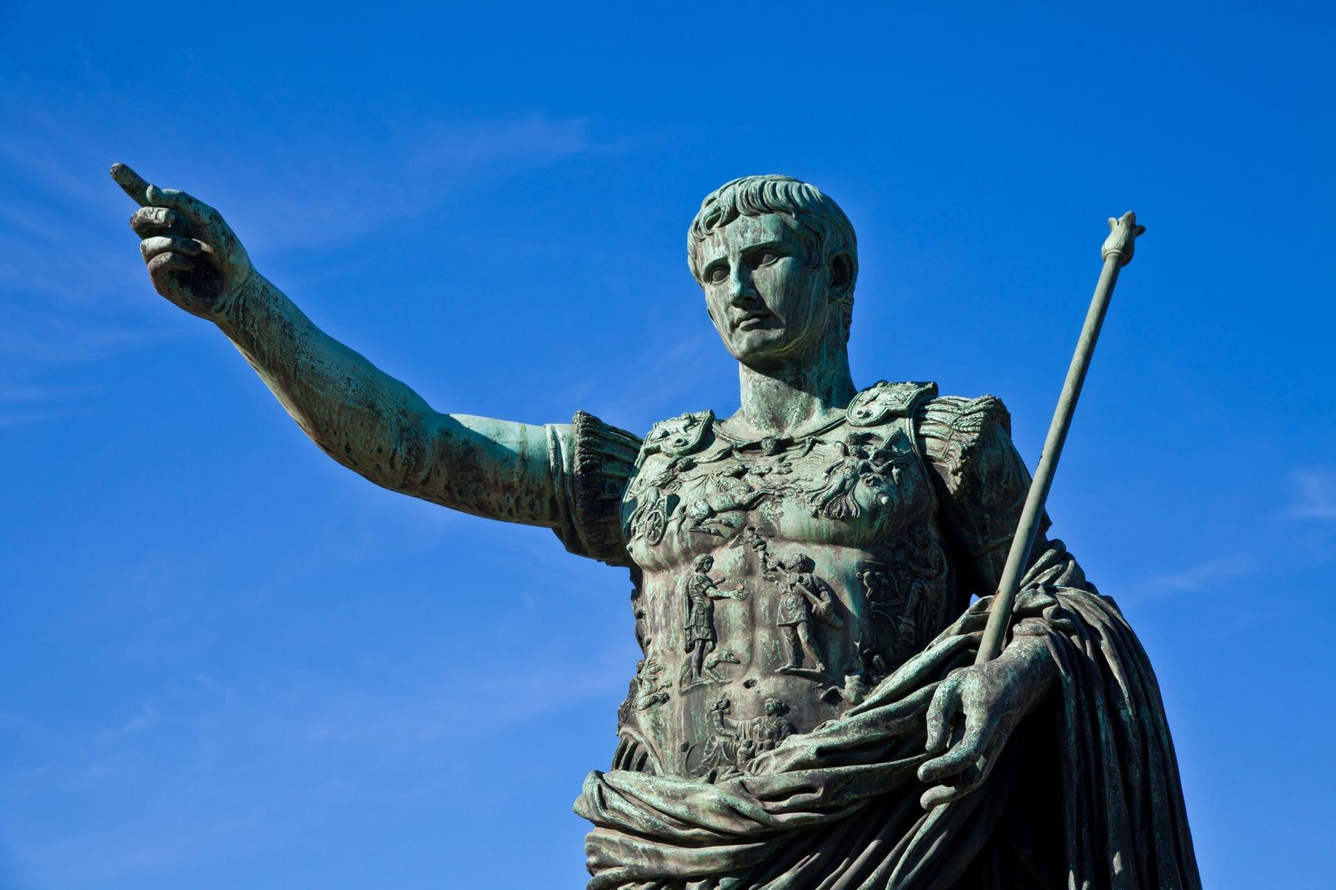 Fotografia nieznanego autora przedstawia posąg Gajusza Juliusza Cezara. Został on przedstawiony jako mężczyzna wśrednim wieku. Cezar ubrany jest wzbroję. Wjednej dłoni trzyma berło, drugą dłoń ma wyciągniętą przed siebie.