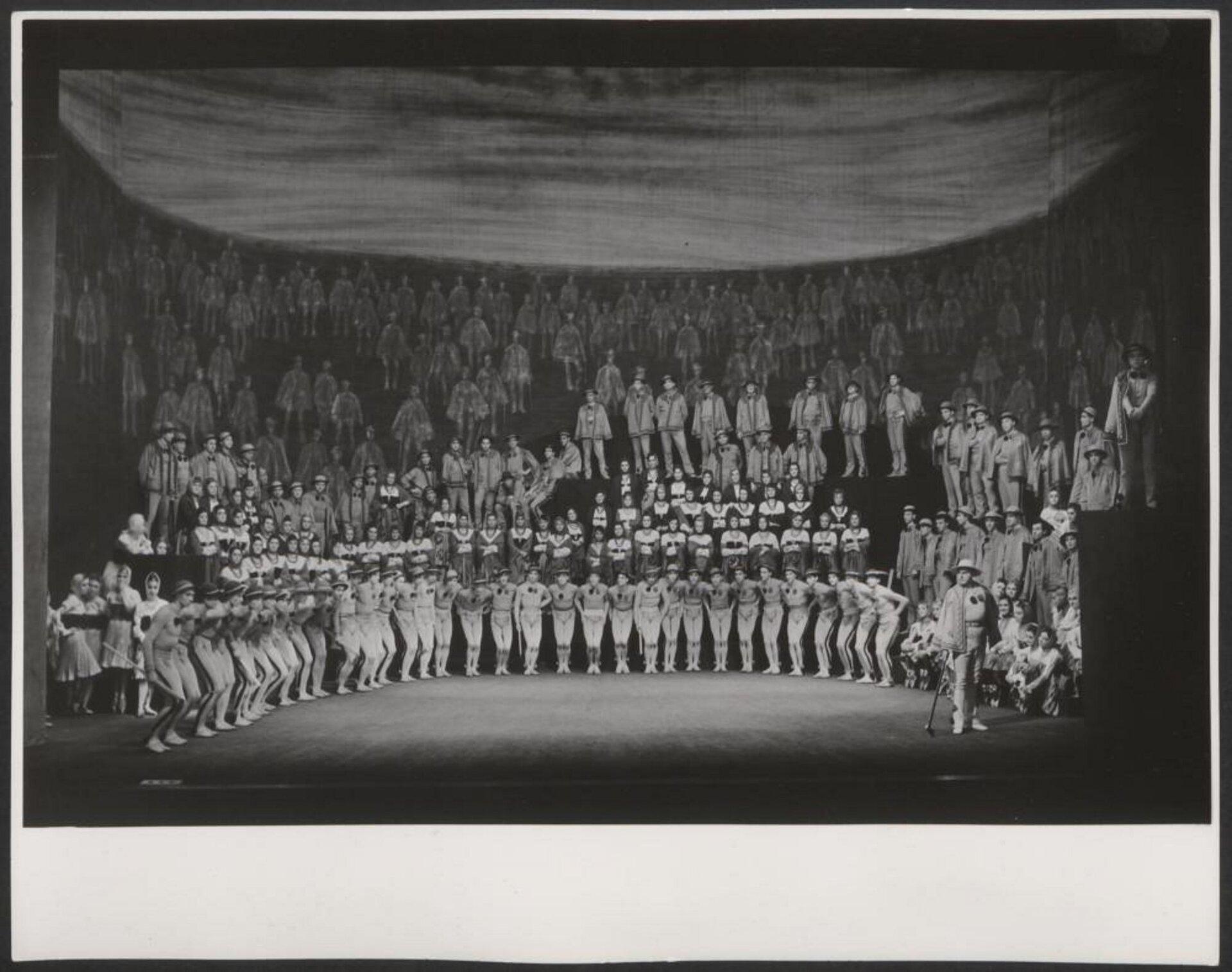 """Fotografia przedstawia Artura Malawskiego, podczas spektaklu z1962 roku """"Wierchy"""". Na scenie znajdują się tłumy osób, ustawionych wrzędzie, można zauważyć, że mężczyźni wpierwszym rzędzie ubrani są wstroje góralskie wjasnych barwach."""
