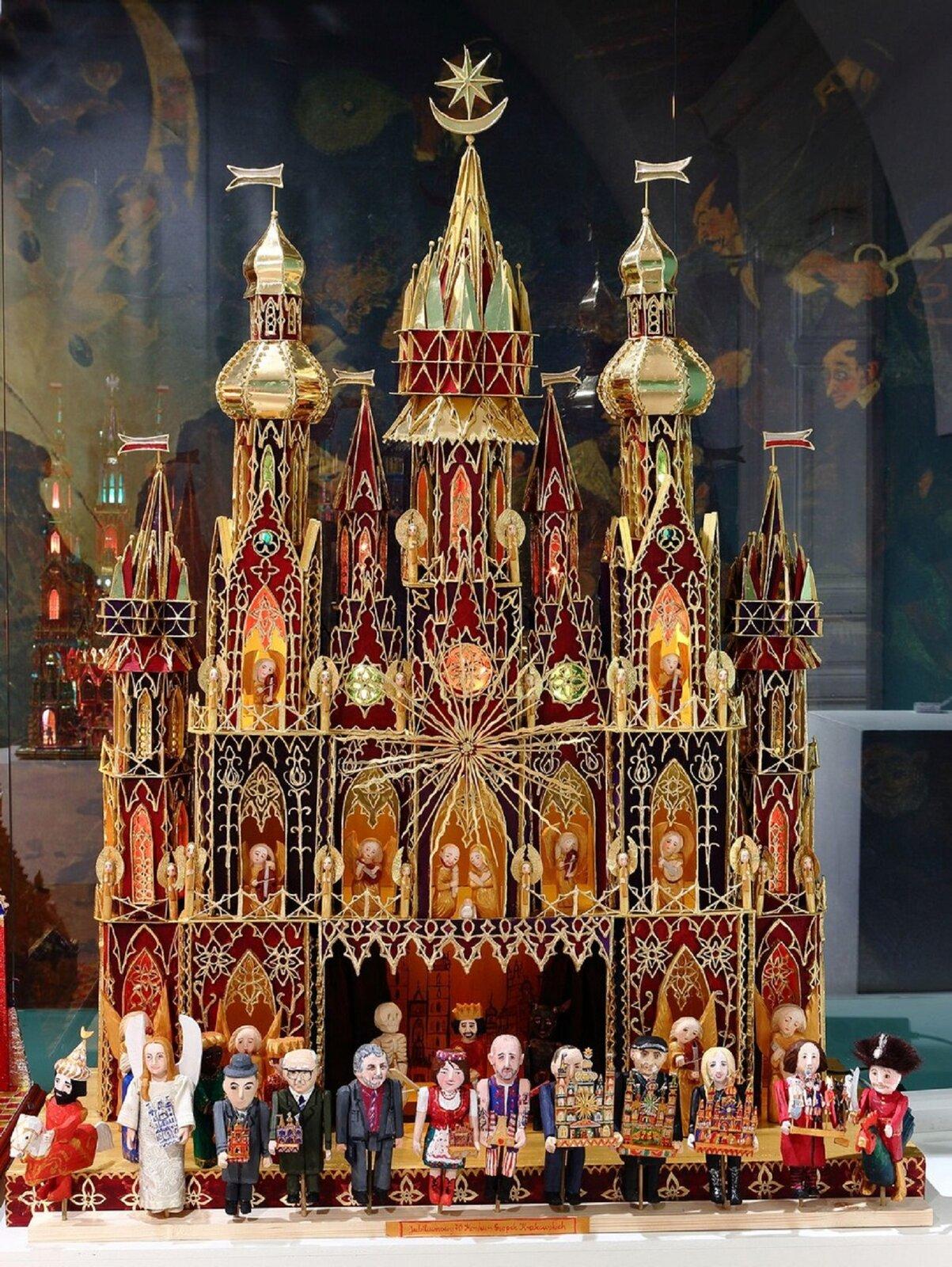 Na zdjęciu szopka bożonarodzeniowa, pochodząca zKrakowa. Szopka podobna jest zdo kościoła zwieżami. Wokienkach umieszczone są figurki. Wgórnych rzędach nieruchome postaci: Jezusa, Maryi, Józefa ianiołów. Wdolnym rzędzie ruchome postaci mieszkańców Krakowa, niektórzy znich niosą wdarze mniejsze szopki.