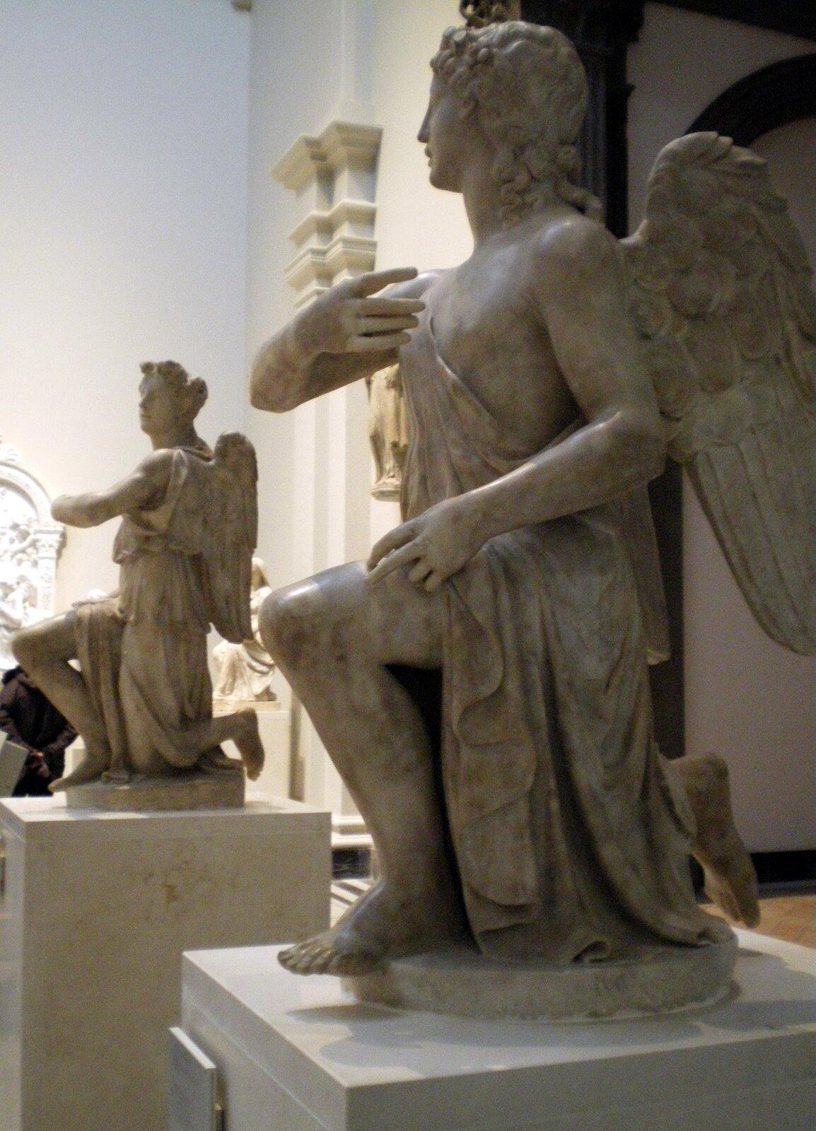Ilustracja przedstawia rzeźby zPalazzo Strozzi autorstwa Silvio Cosiniego. Na zdjęciu znajdują się dwie rzeźby klęczących na jednym kolanie, marmurowych aniołów. Umieszczone na oddzielnych, sześciennych postumentach posągi stoją wsali muzeum. Ubrane są wspływające drobnymi fałdami tuniki przepasane wpasie. Ich włosy opadają falami loków na ramiona. Anioł znajdujący się na pierwszym planie ma skierowaną głowę na prawo. Anioł wgłębi kadru kieruje głowę na lewo.