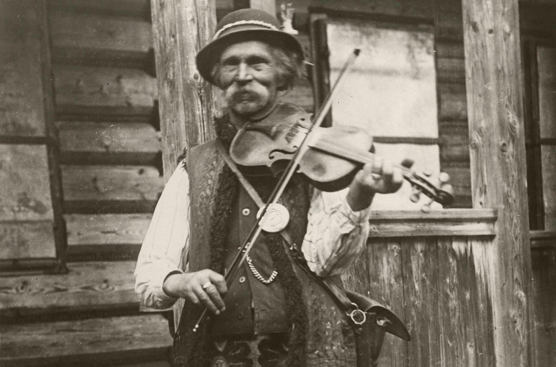 Fotografia przedstawia Bartusia Obrochtę. Starszy mężczyzna zuśmiechem, stoi igra na skrzypcach. Ubrany jest wstrój góralski. Wtle widać drewnianą, zniszczoną chatę.