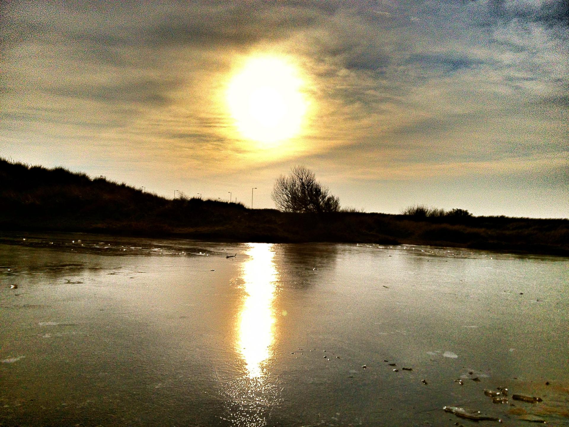 Zdjęcia przedstawiające pokrywę lodową na jeziorze, na którą świeci słońce – wyraźnie widoczne promienie słoneczne padające na powierzchnię lodu
