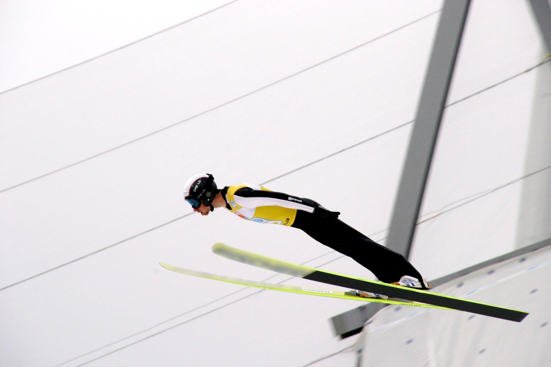 Zdjęcie przedstawia skoczka narciarskiego wpowietrzu tuż po wyjściu zprogu. Jest on zwrócony wlewą stronę kadru, aciało układa się już wsylwetkę odpowiednią do układu V. Tło jest białe, kombinezon sportowca ijego narty są czarno żółte.