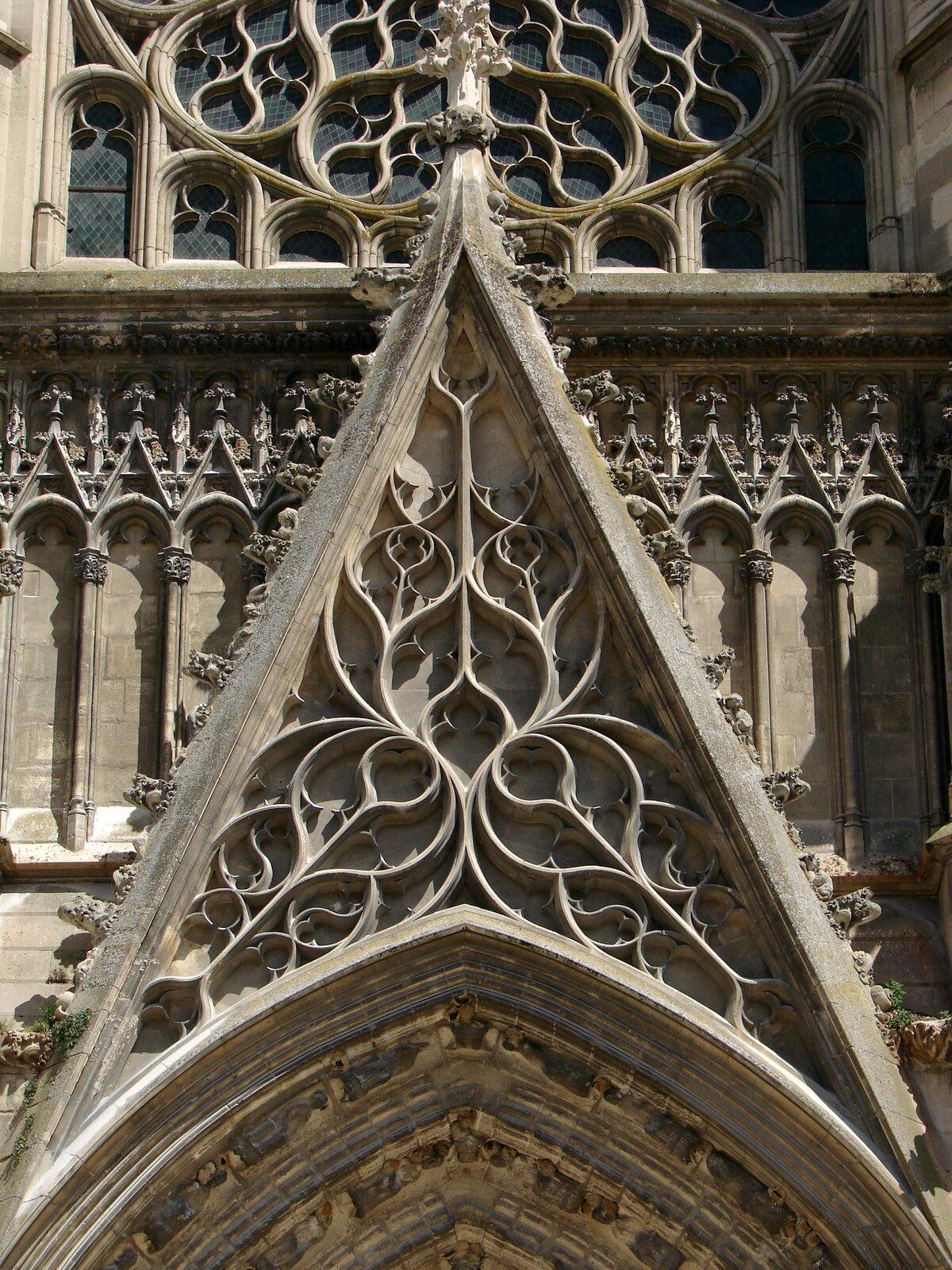 Fasada katedry wMeaux Wimperga – ażurowe trójkątne szczyty portalowe lub okienne. Ich wnętrze wypełniano maswerkiem, krawędzie ozdabiano żabkami, wieńczono kwiatonem lub pinaklem. Źródło: Fasada katedry wMeaux, licencja: CC BY-SA 3.0.